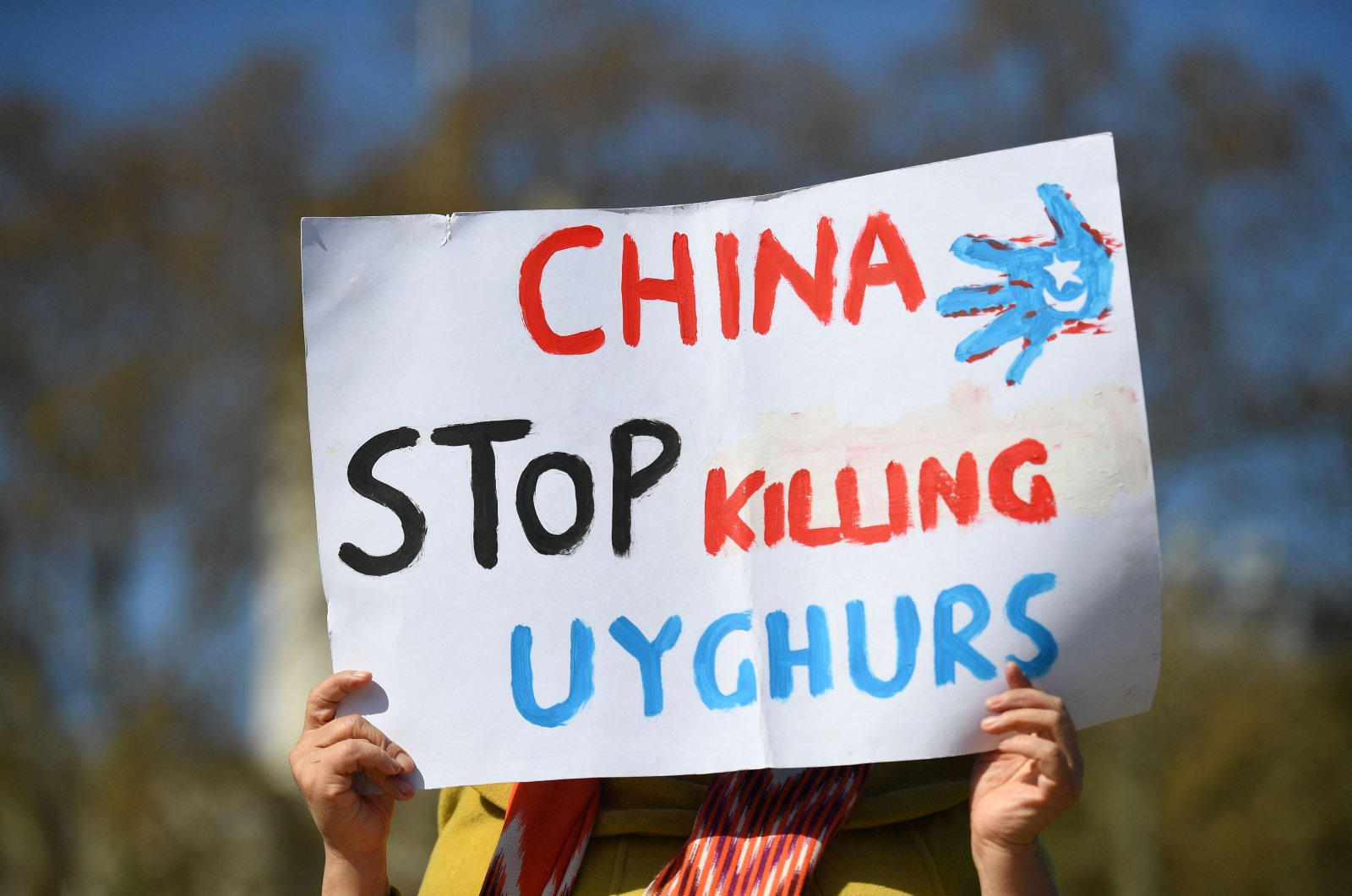 A member of the Uyghur community holds a placard as she joins a demonstration to call on the British parliament to vote to recognize persecution of China's Muslim minority Uyghur people as genocide and crimes against humanity in London, U.K., April 22, 2021. (AFP Photo)
