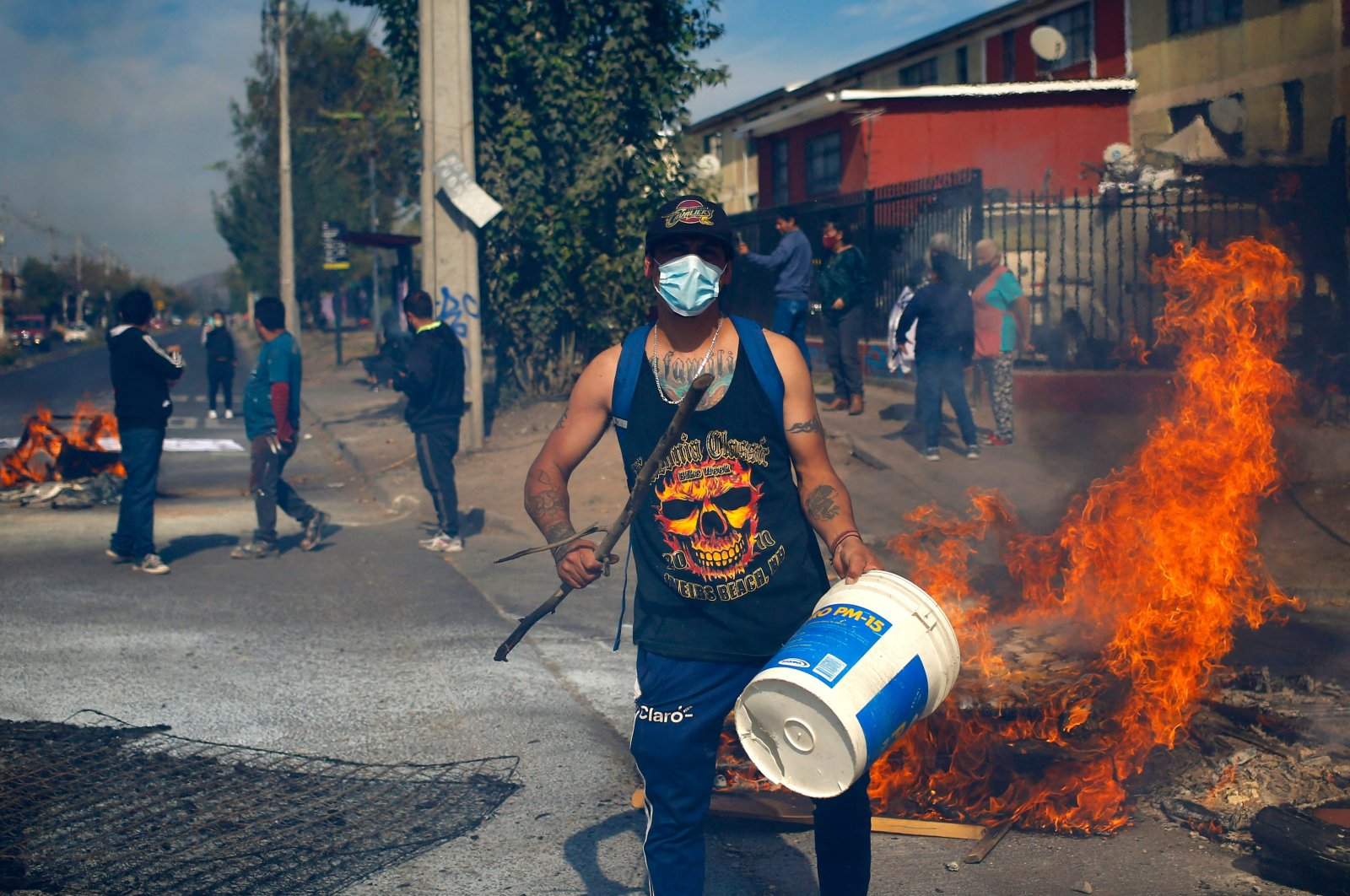 People protest amid burning barricades in demand of economic help from the government and the approval of the third early withdrawal of pension funds amid the crisis triggered by the COVID-19 pandemic at the Pintana poor commune, in Santiago, Chile, April 22, 2021. (AFP Photo)