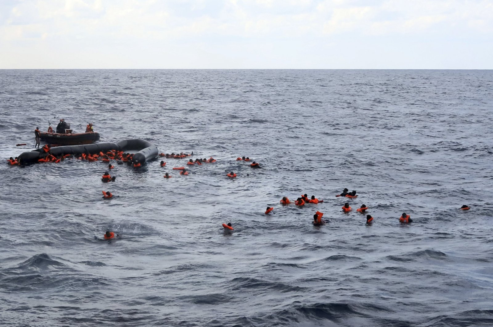 Refugees and migrants are rescued by members of the Spanish NGO Proactiva Open Arms, after leaving Libya trying to reach European soil aboard an overcrowded rubber boat in the Mediterranean sea, Nov. 11, 2020. (AP File Photo)