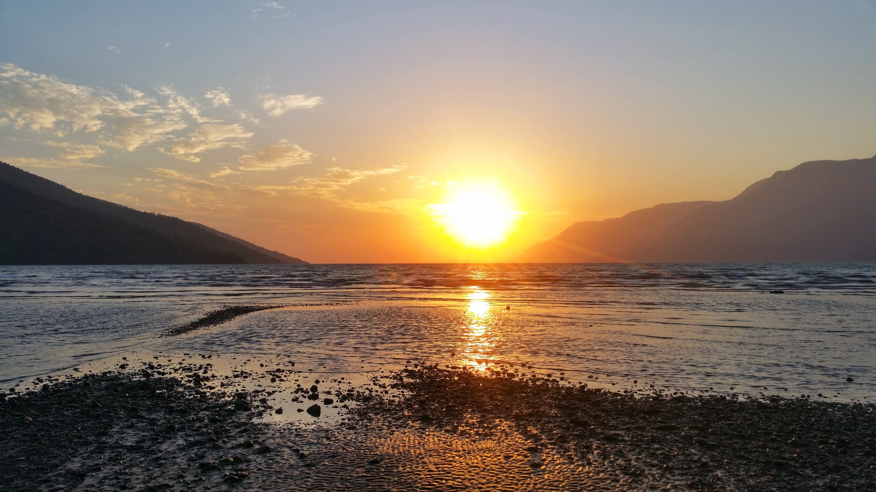 Across from a beach, the sun sets over the mountains in Akyaka, Muğla, Turkey. (Shutterstock Photo)