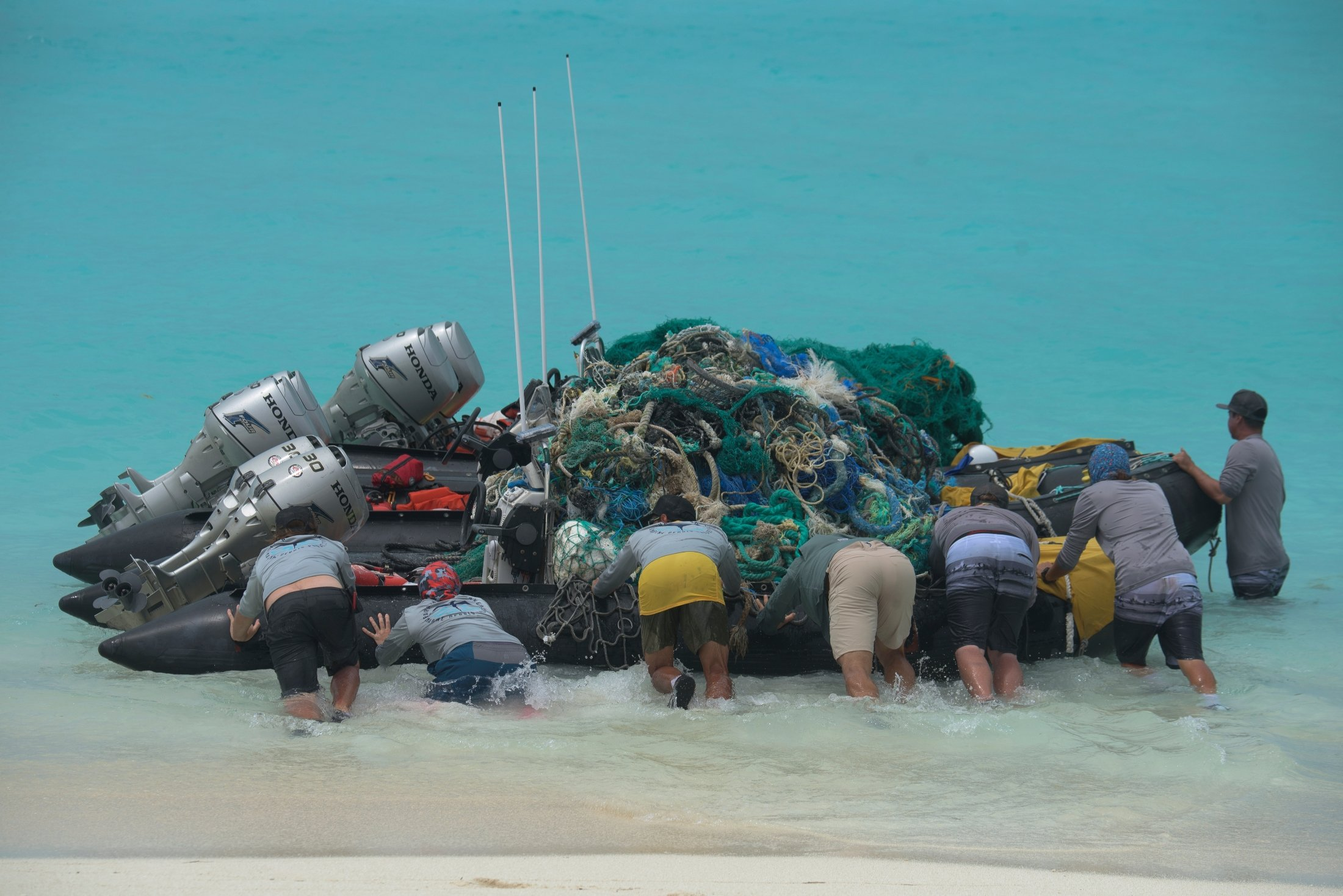 Workers with the Papahanaumokuakea Marine Debris Project push small boats loaded with fishing nets and plastic off Kure Atoll in the Northwestern Hawaiian Islands, Hawaii, April 10, 2021. (Papahanaumokuakea Marine Debris Project via AP)