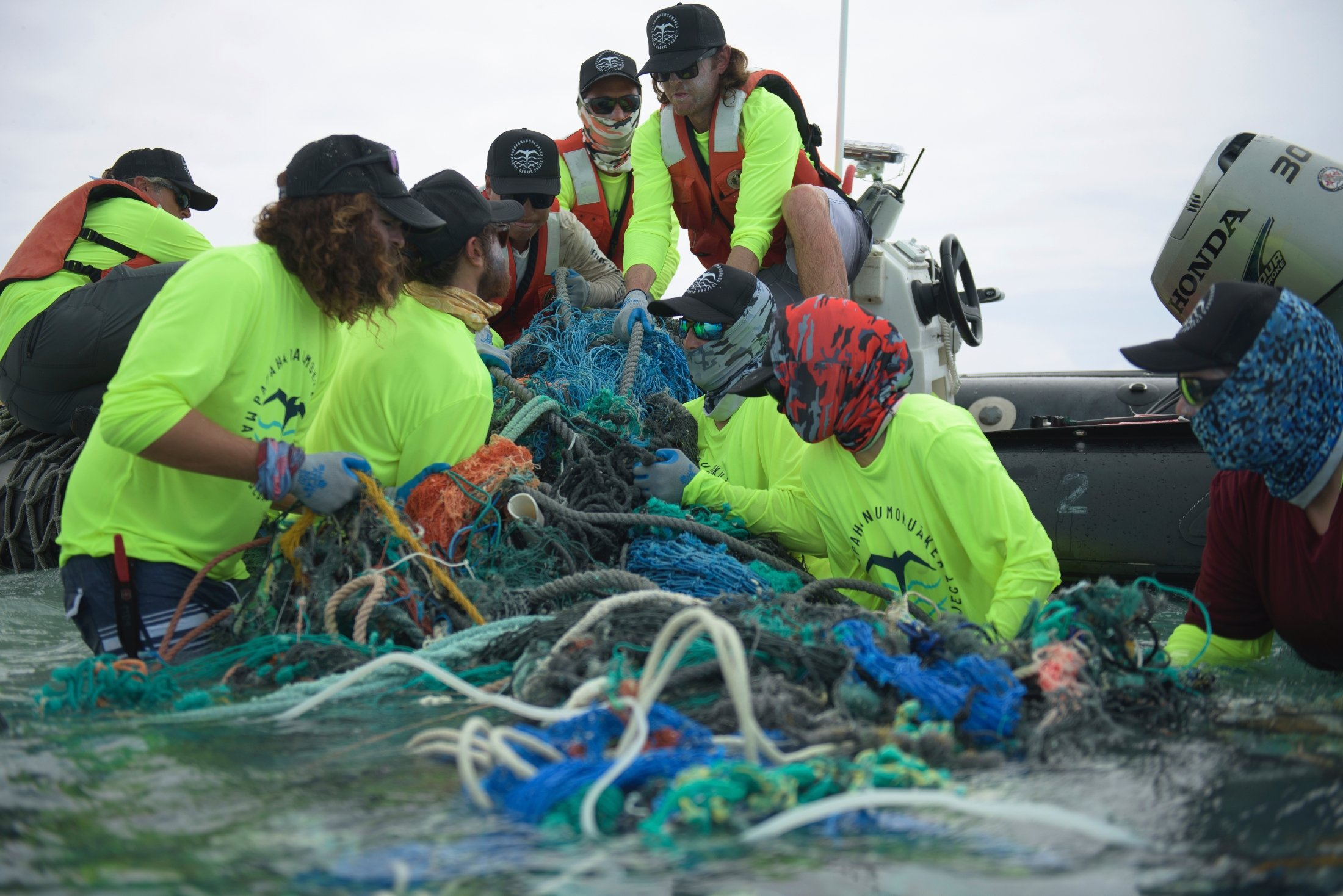 Workers with the Papahanaumokuakea Marine Debris Project load fishing nets onto a small boat on Midway Atoll in the Northwestern Hawaiian Islands, Hawaii, April 8, 2021. (Papahanaumokuakea Marine Debris Project via AP)