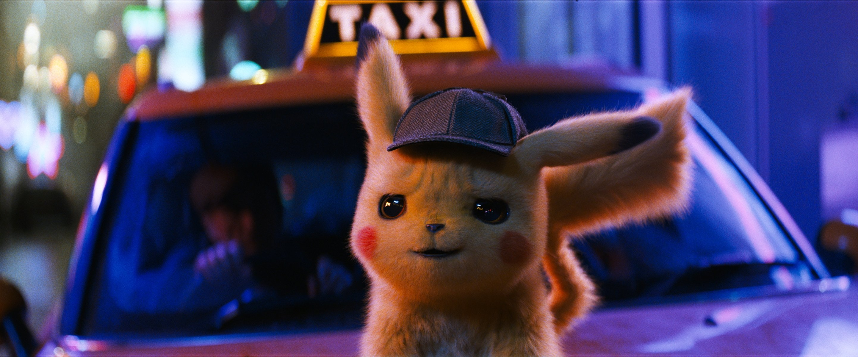 """The character """"Detective Pikachu,"""" voiced by Ryan Reynolds, stands atop a taxi car, in a scene from 'Pokemon Detective Pikachu.' (Warner Bros. Pictures via AP)"""
