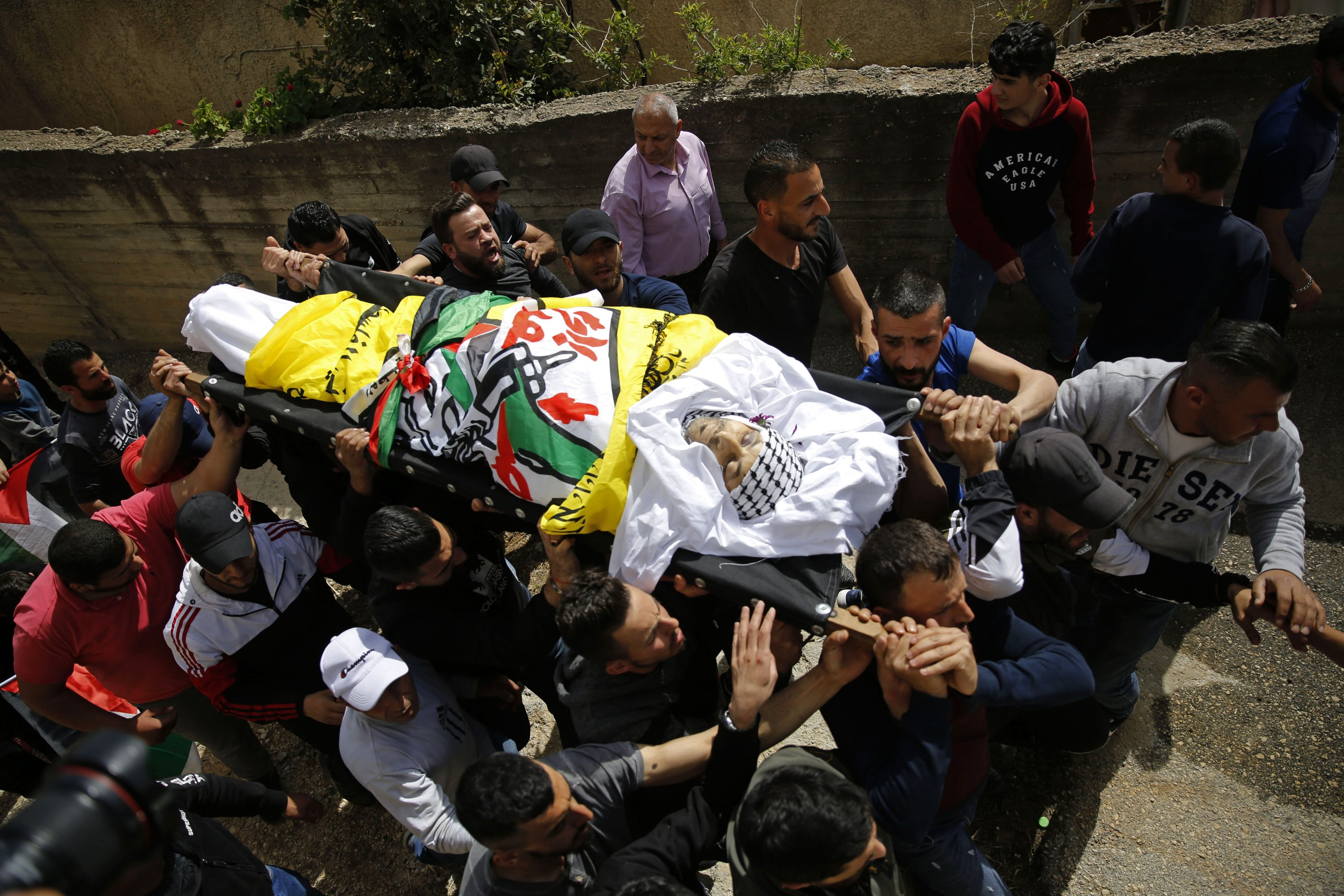 Palestinians carry the body of Osama Mansour who was killed by Israel soldiers at a temporary vehicle checkpoint in the occupied West Bank near Jerusalem, during his funeral, in the village of Biddu near the West Bank city of Ramallah,  April 6, 2021. (AP Photo)