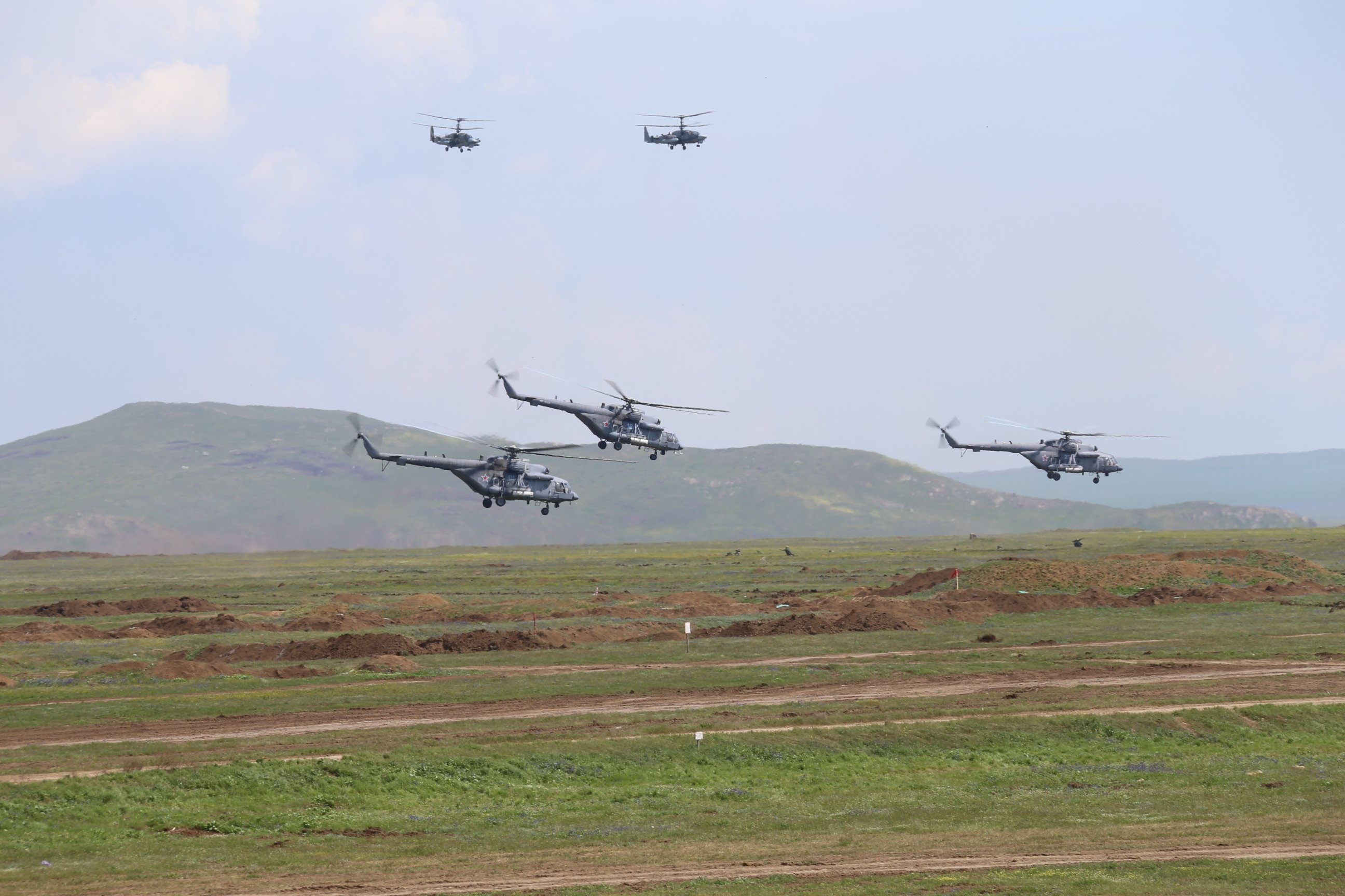 Russian military helicopters taking part in a military drill over the Opuk training ground not far from the town of Kerch, on the Kerch Peninsula in the east of Crimea, in this handout picture released by the Russian Defense Ministry on April 22, 2021. (Photo by Vadim Savitsky / Russian Defense Ministry / AFP)