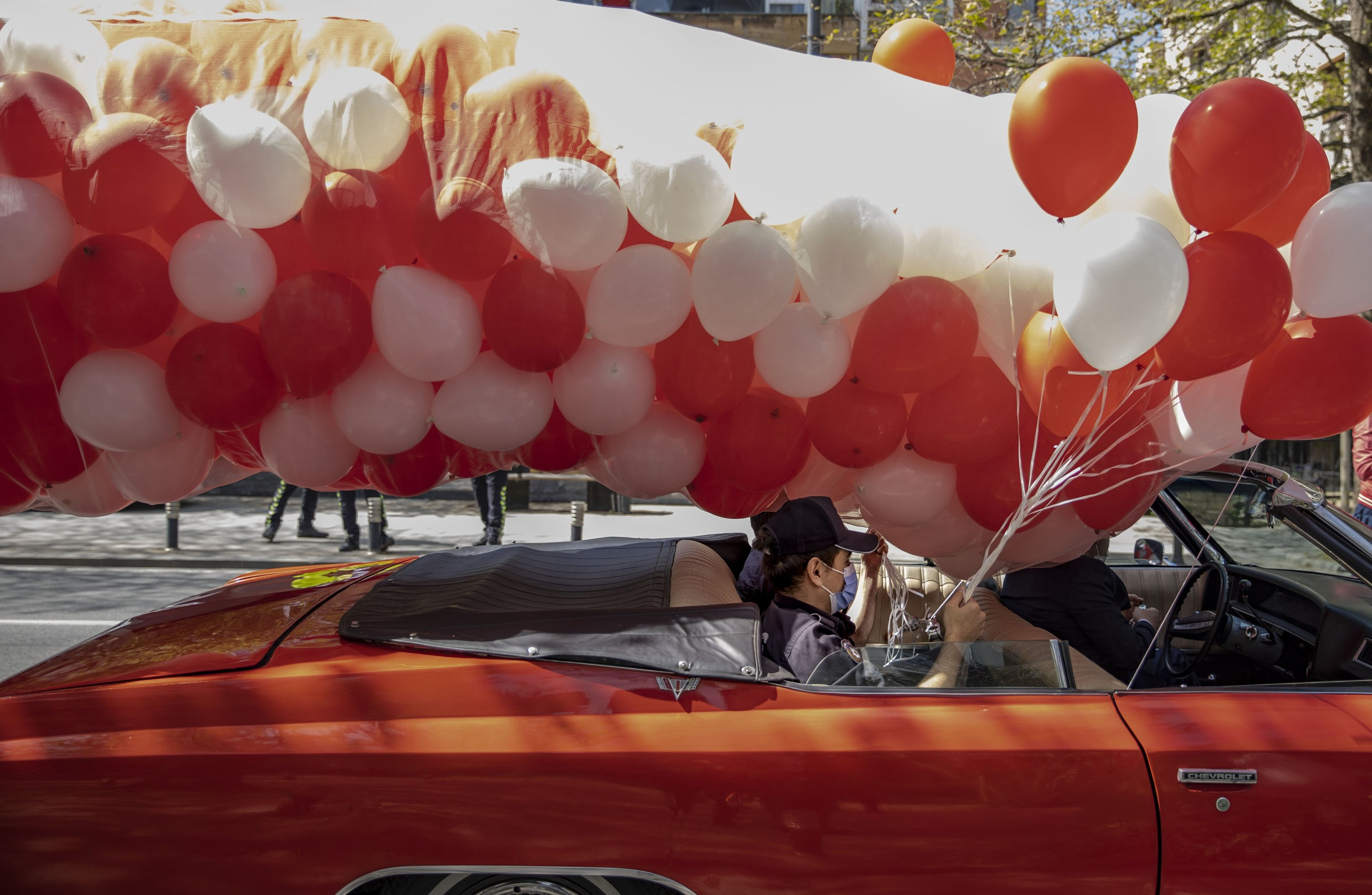 Members of the Istanbul police department release red and white balloons from a classic convertibleas part of the National Sovereignty and Children's Day celebrations, in Istanbul, Turkey, April 23, 2021. (AA Photo)