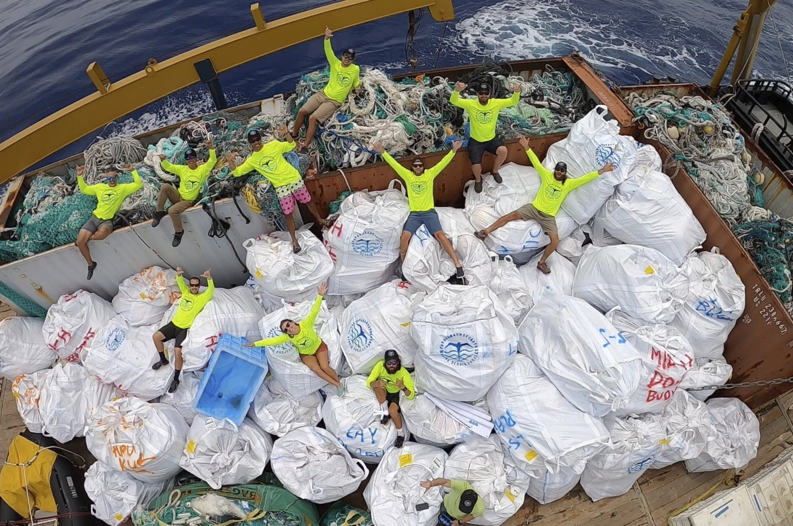 Workers with the Papahanaumokuakea Marine Debris Project pose on top of fishing nets and plastics collected from the the beaches of the Northwestern Hawaiian Islands, Hawaii, April 21, 2021. (Papahanaumokuakea Marine Debris Project via AP)