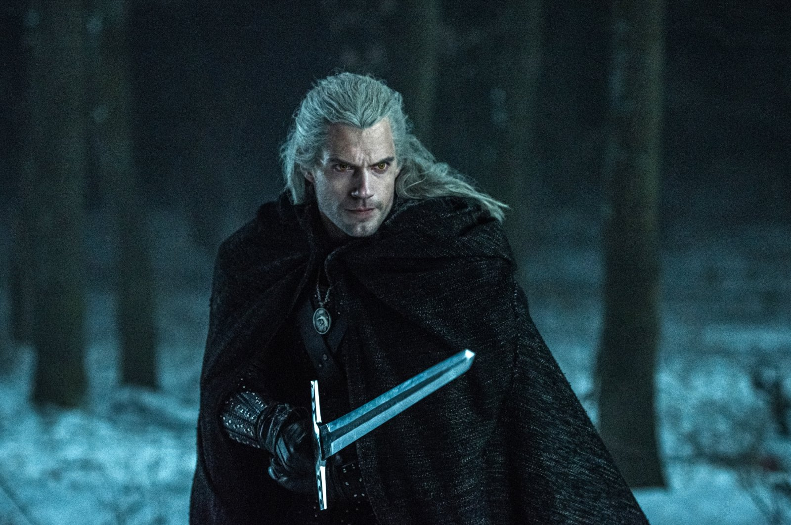 """Actor Henry Cavill portrays """"Geralt of Rivia"""", wielding a sword in a forest covered with snow, in a scene from the Netflix TV series """"The Witcher,"""" based on a fantasy novel series that found fame as a video game. (Netflix via AP)"""