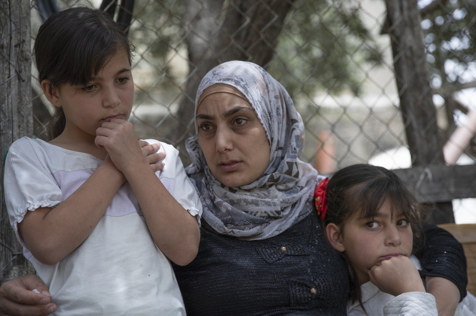 Somaya, the wife of Palestinian Osama Mansour, who was shot to death by Israeli soldiers at a temporary checkpoint in the occupied West Bank earlier this month, holds their 10 year-old twins Nissan, left and Bissan, right, at their family house, in the West Bank village of Biddu, west of Ramallah, Tuesday, April 20, 2021. (AP Photo)