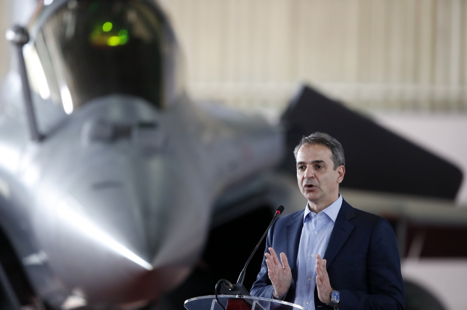 Greece's Prime Minister Kyriakos Mitsotakis speaks during the international military exercise Iniochos with a French Rafale fighter jet in the background, at Andravida air base, about 279 kilometers (174 miles) southwest of Athens, Greece, April 20, 2021. (AP Photo)