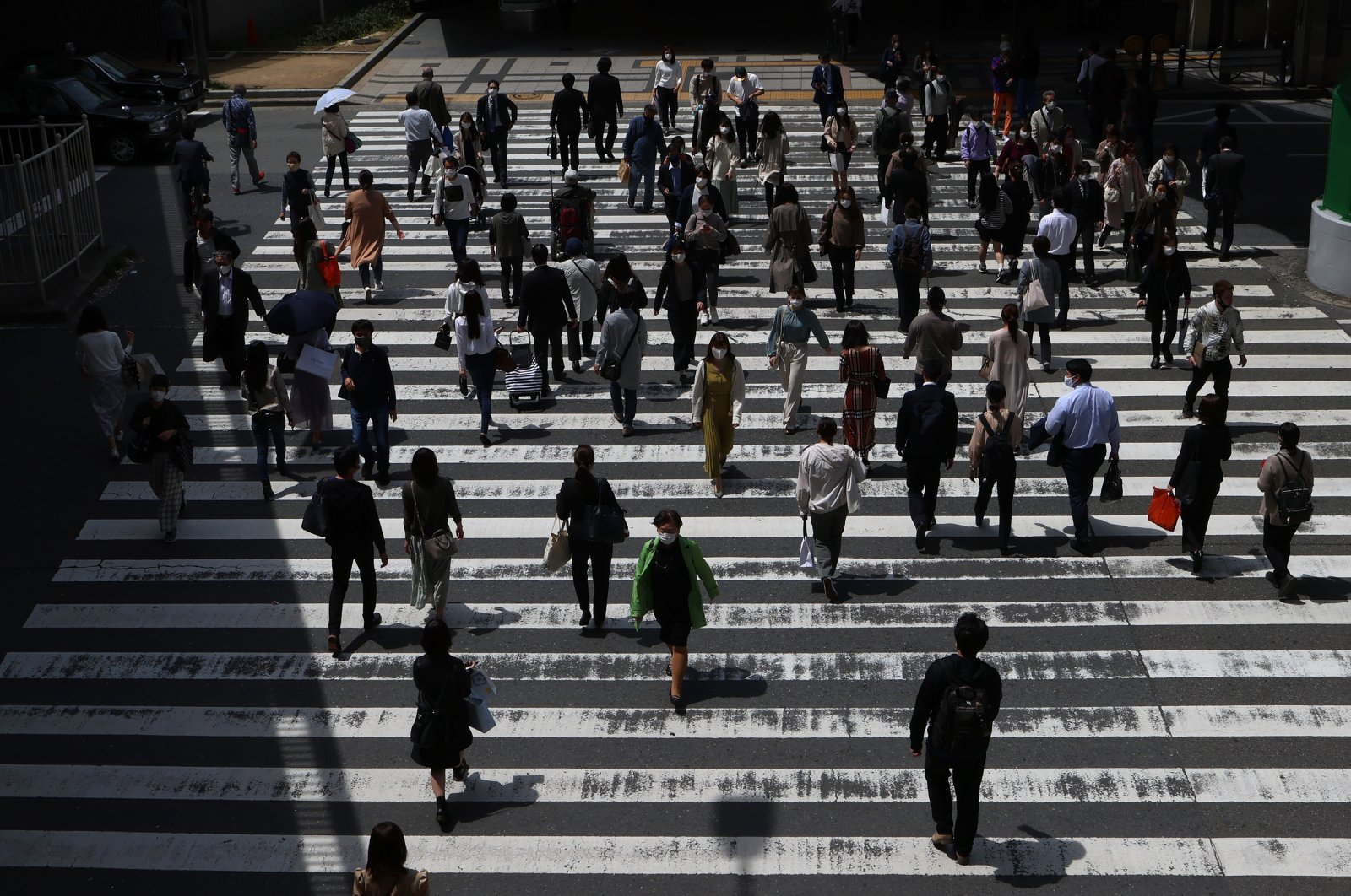 People wearing protective face masks cross a street, Osaka, Japan, April 23, 2021. (Photo by Getty Images)