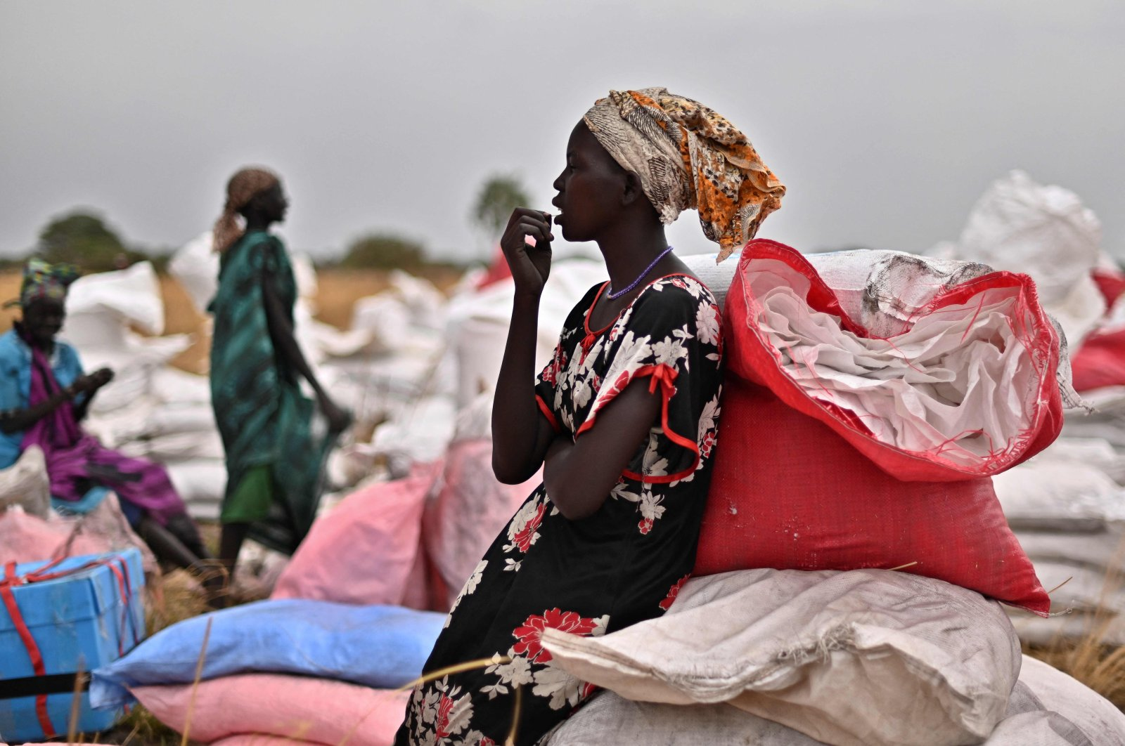 A villager who volunteered to fetch gunny bags containing food rations from the site of an airdrop takes a break at a village in Ayod county, South Sudan, Feb. 6, 2020. (AFP Photo)
