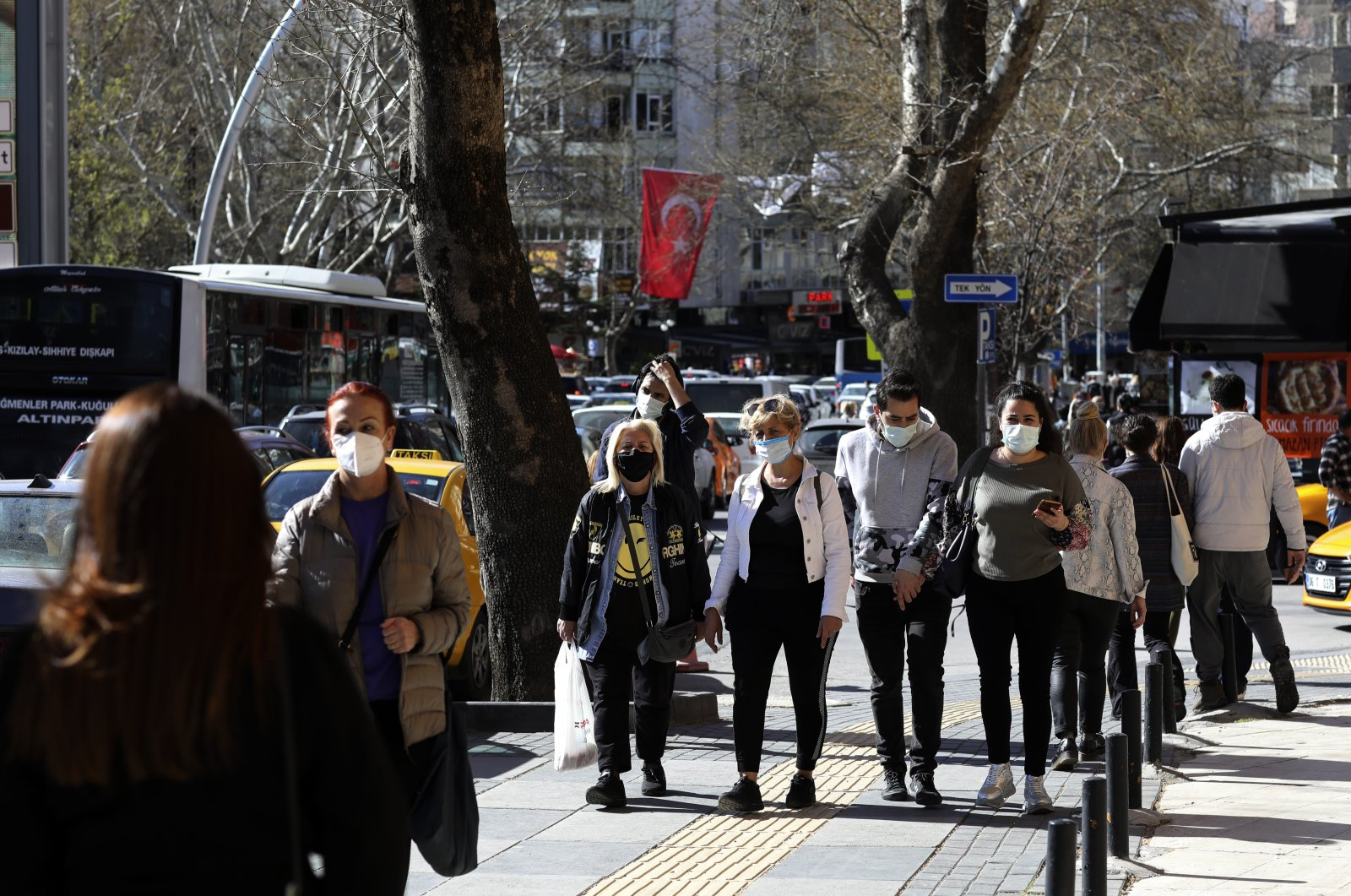 People wearing masks to help protect against the spread of coronavirus, walk along a busy street before a nationwide lockdown, in Ankara, Turkey, April 22, 2021. (AP)