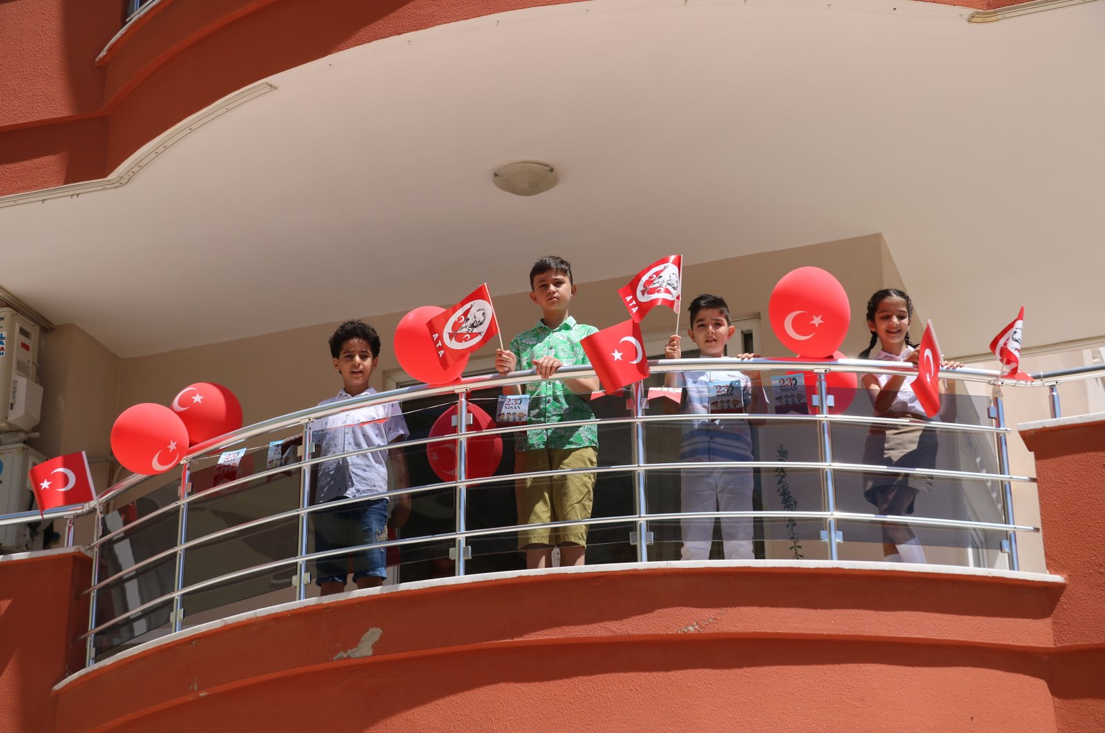 Children confined to home due to pandemic, wave flags and balloons at the balcony of their home, in Alanya district, in Antalya, southern Turkey, Apr. 23, 2021. (İHA PHOTO)