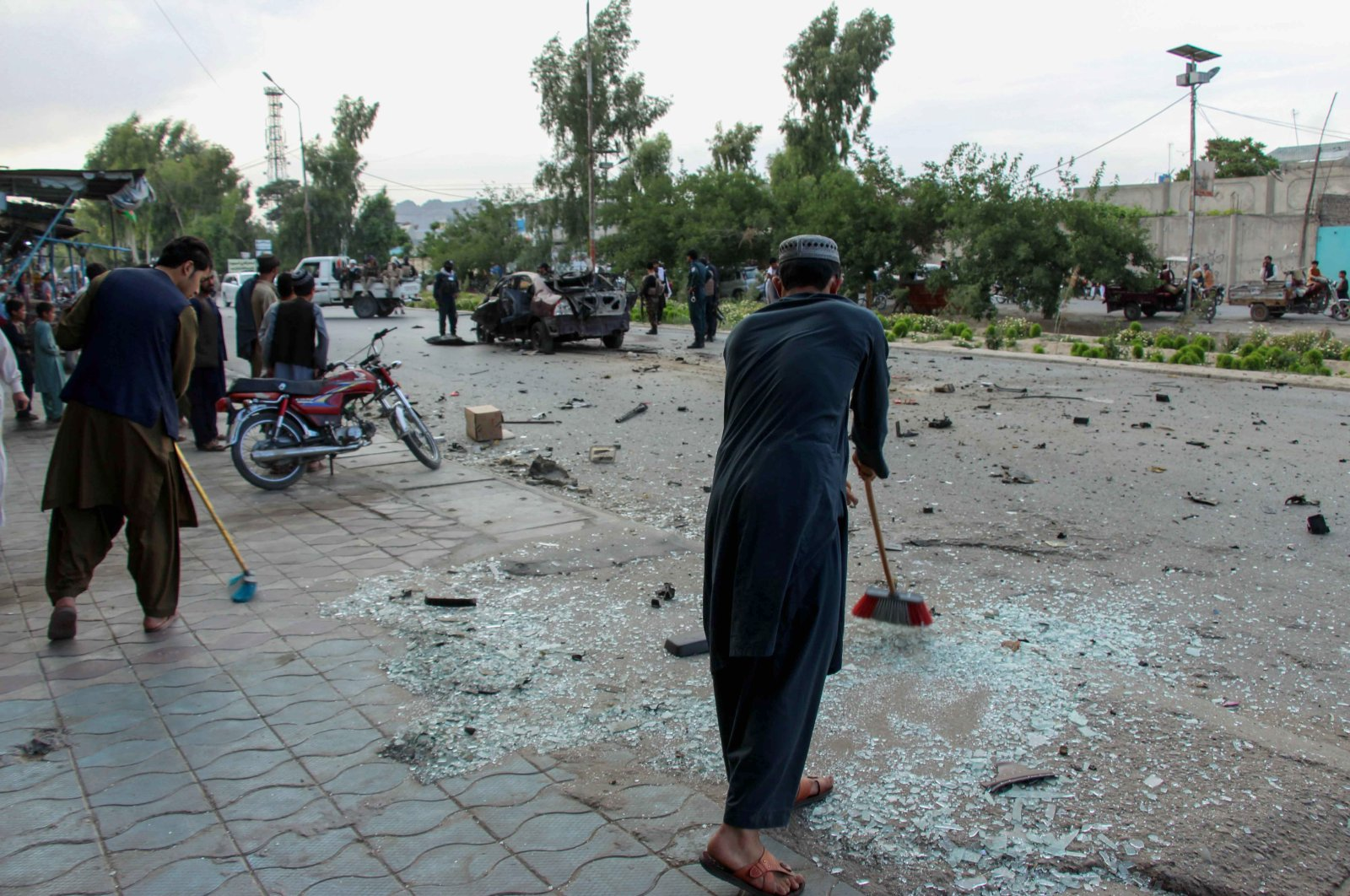 People remove smashed glass at the scene of a landmine explosion that targeted a vehicle of a local police commander, in Kandahar, Afghanistan, April 19, 2021. (EPA Photo)