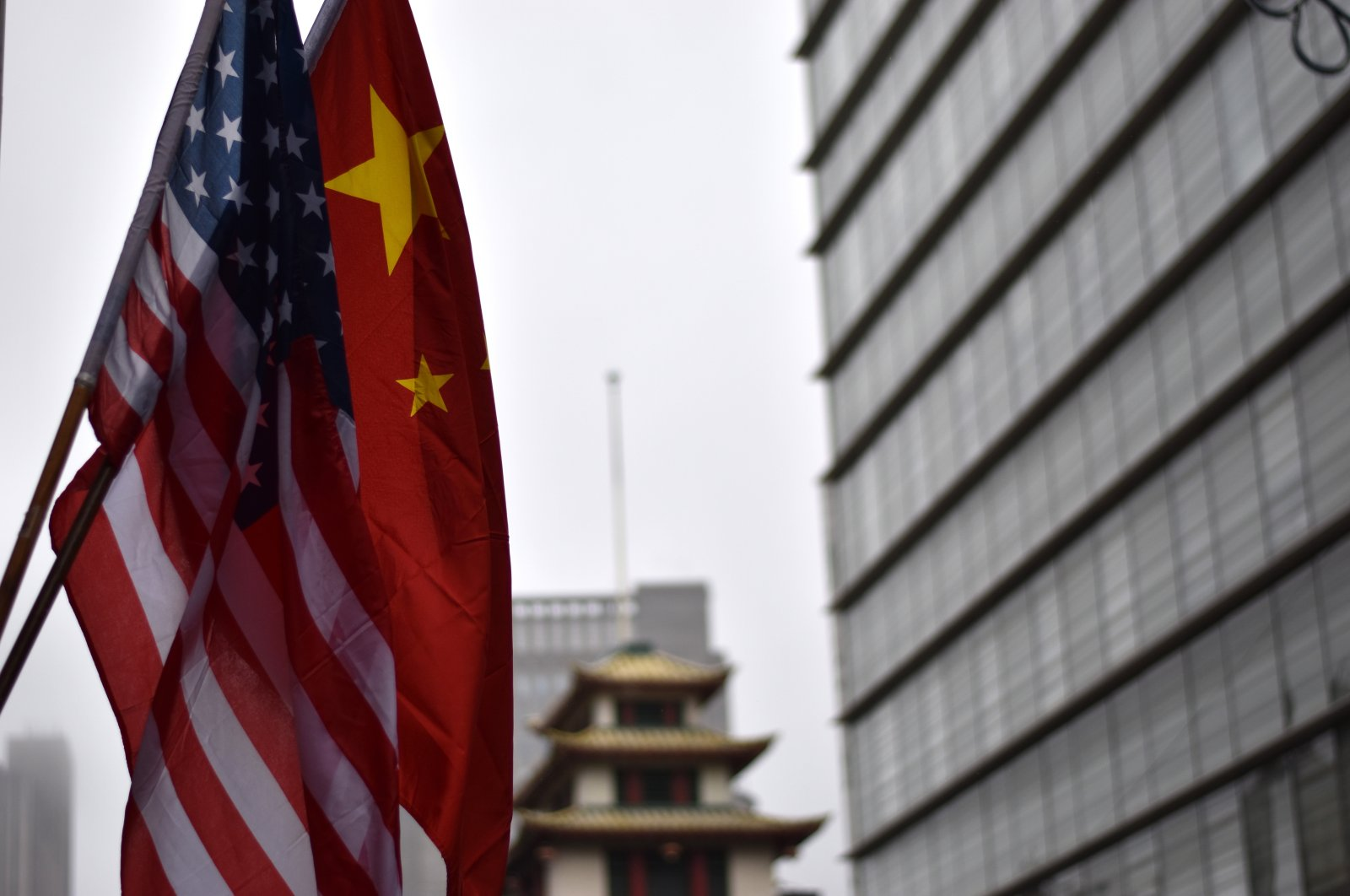 The flags of the U.S. and China hang on a building in a Chinatown in New York City, U.S., Feb. 25, 2018. (Photo by Shutterstock)