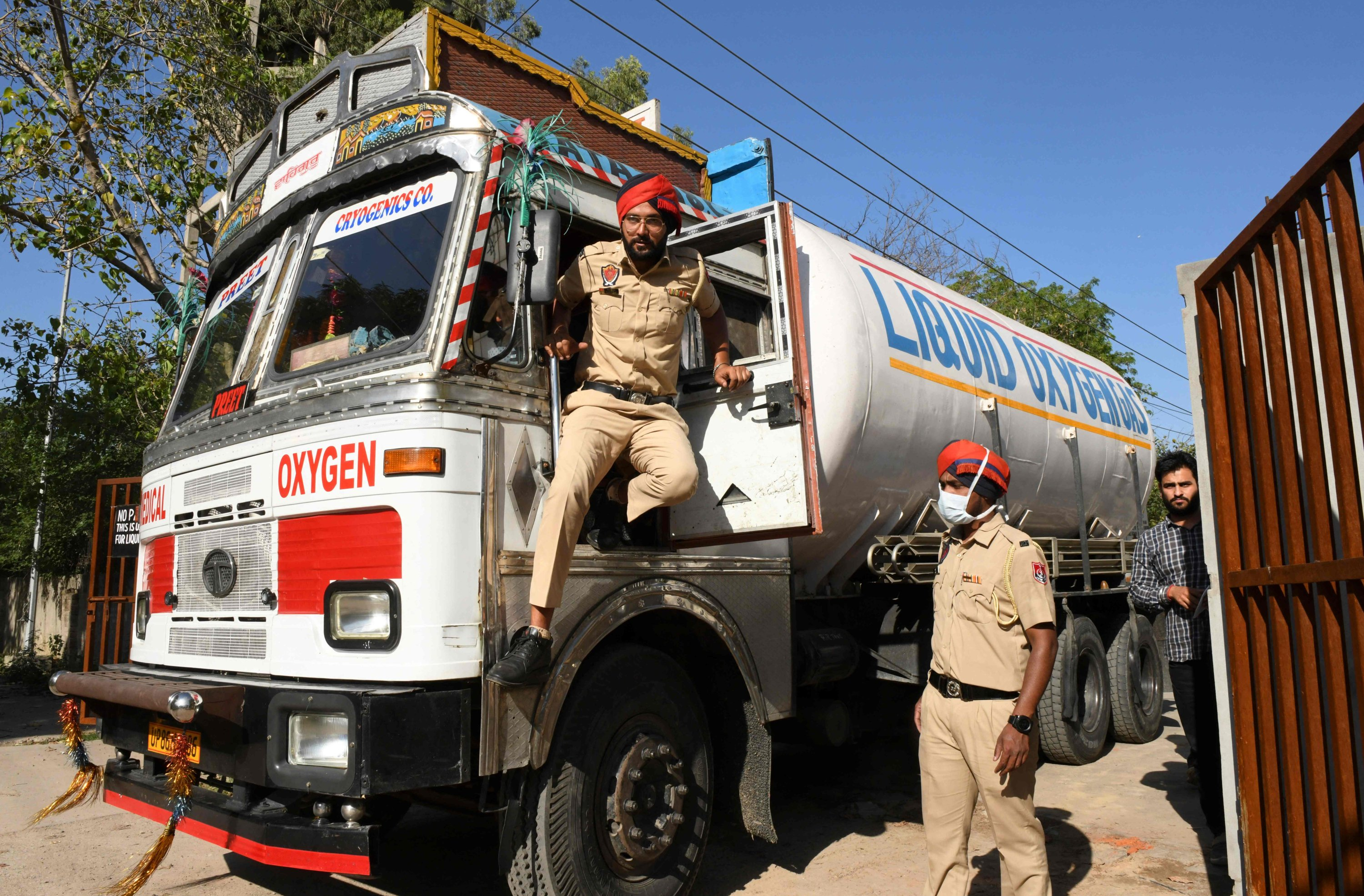 Police personnel prepare to escort a truck carrying medical liquid oxygen atthe Guru Nanak Dev hospital amid COVID-19 pandemic, in Amritsar, India, April 24, 2021. (AFP Photo)