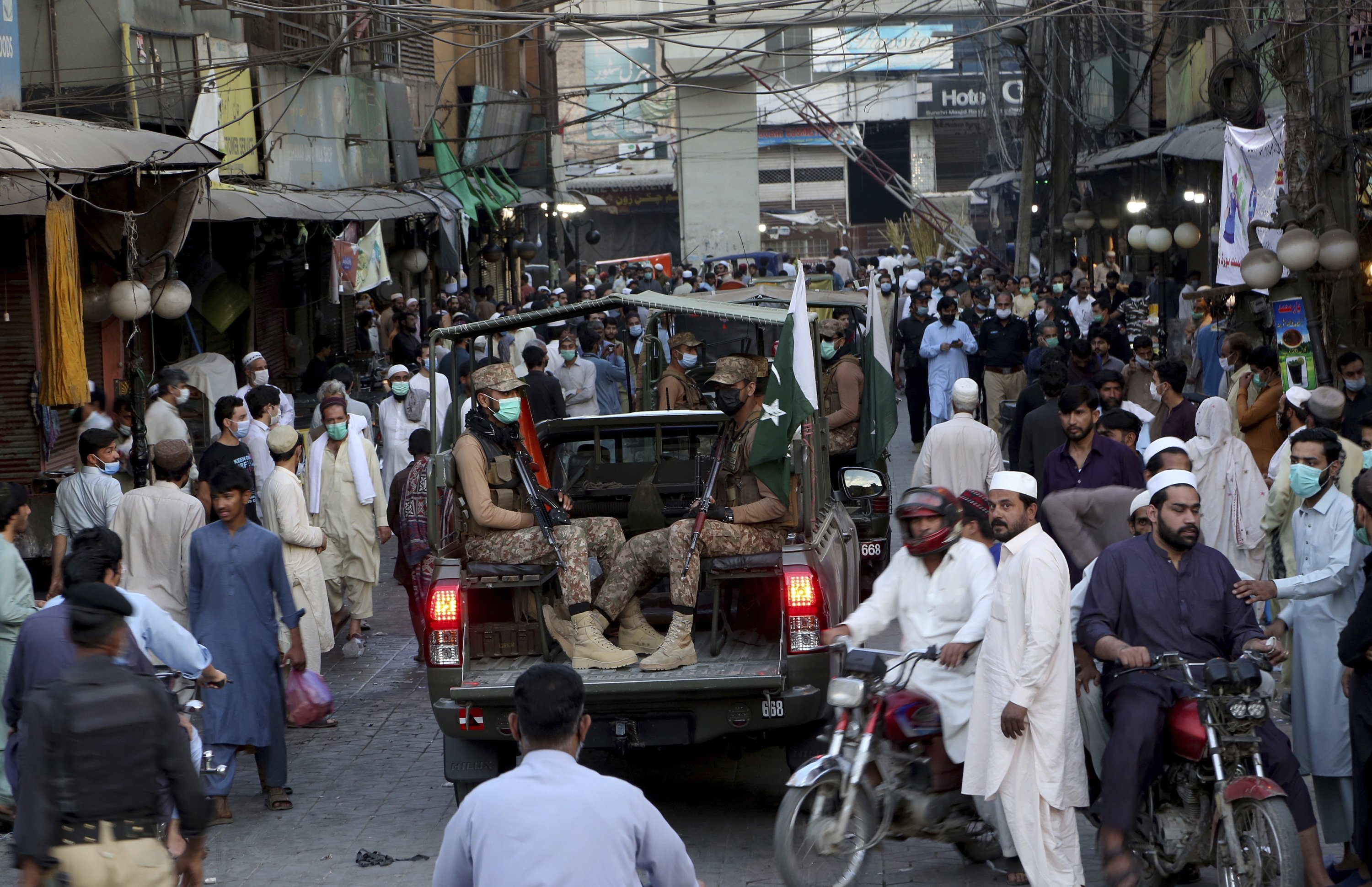 Pakistan army troops arrive to ensure new timing of market closing announced by government to control the spread of the coronavirus, in Peshawar, Pakistan, April 24, 2021. (AP Photo)