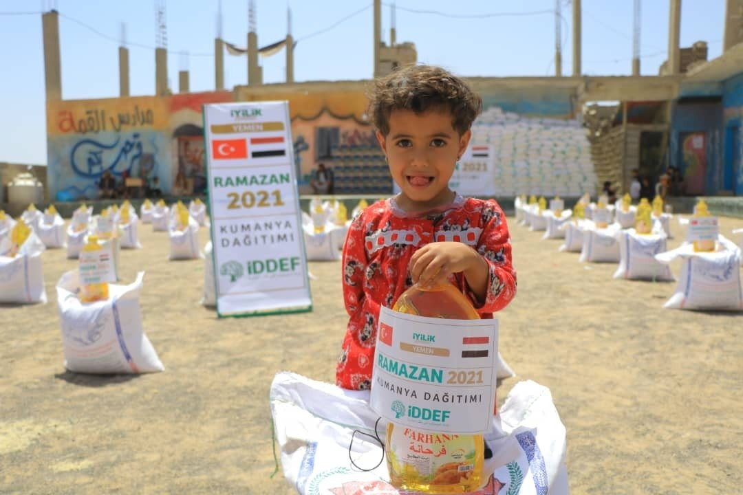 A girl poses with an aid package delivered by a Turkish charity, in Marib, Yemen, April 23, 2021. (İHA PHOTO)