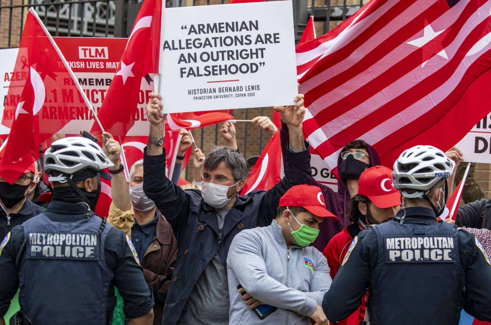 """Supporters of Turkey carrying a sign that reads prominent historian Bernard Lewis' quote """"Armenian allegations are an outright falsehood"""" face off with Armenian supporters outside the Turkish Embassy, Washington, D.C., U.S., April 24, 2021. (AFP Photo)"""
