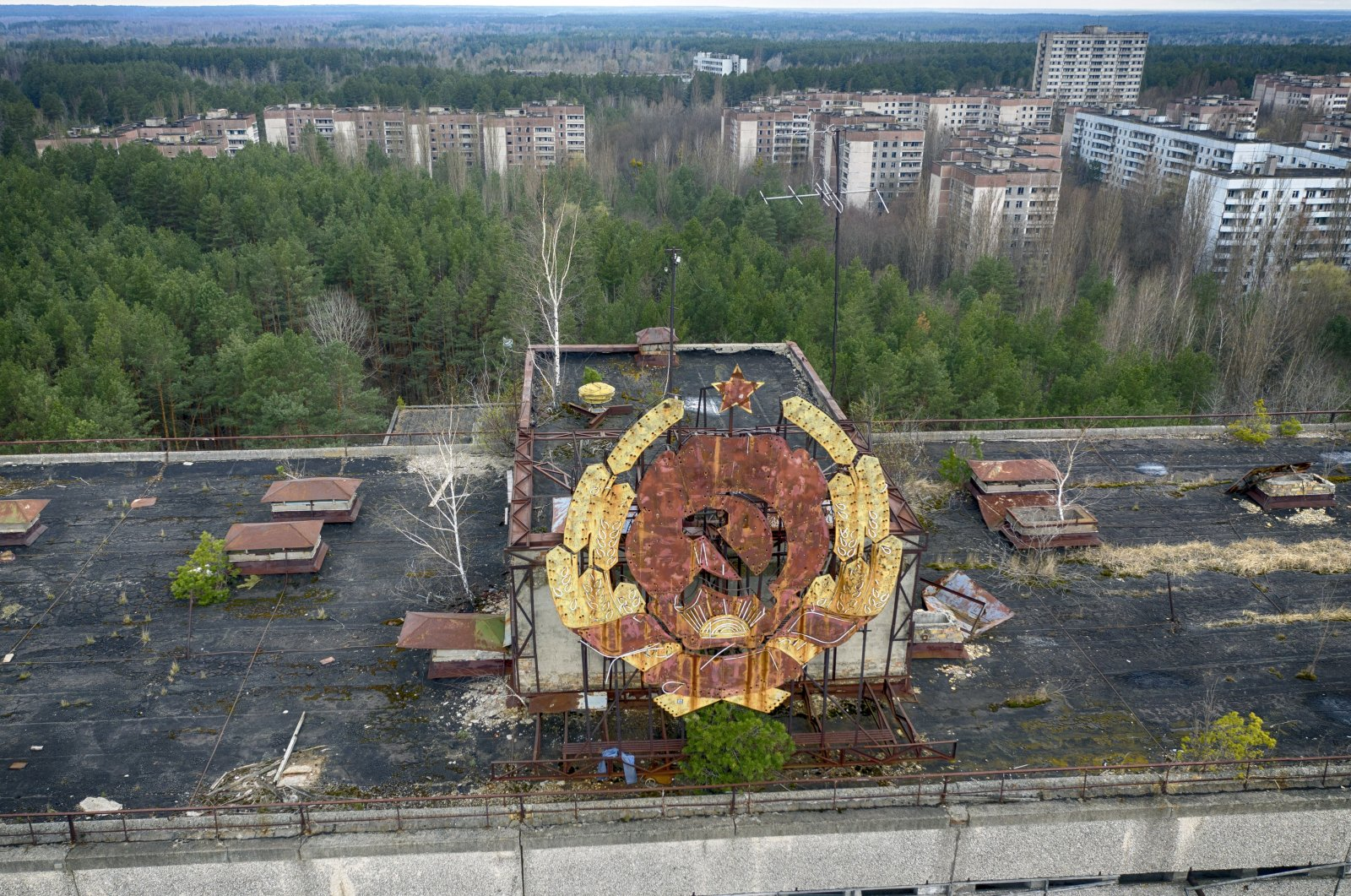 The rusty emblem of the Soviet Union is seen over the ghost town of Pripyat close to the Chernobyl nuclear plant, Ukraine, April 15, 2021. (AP Photo)