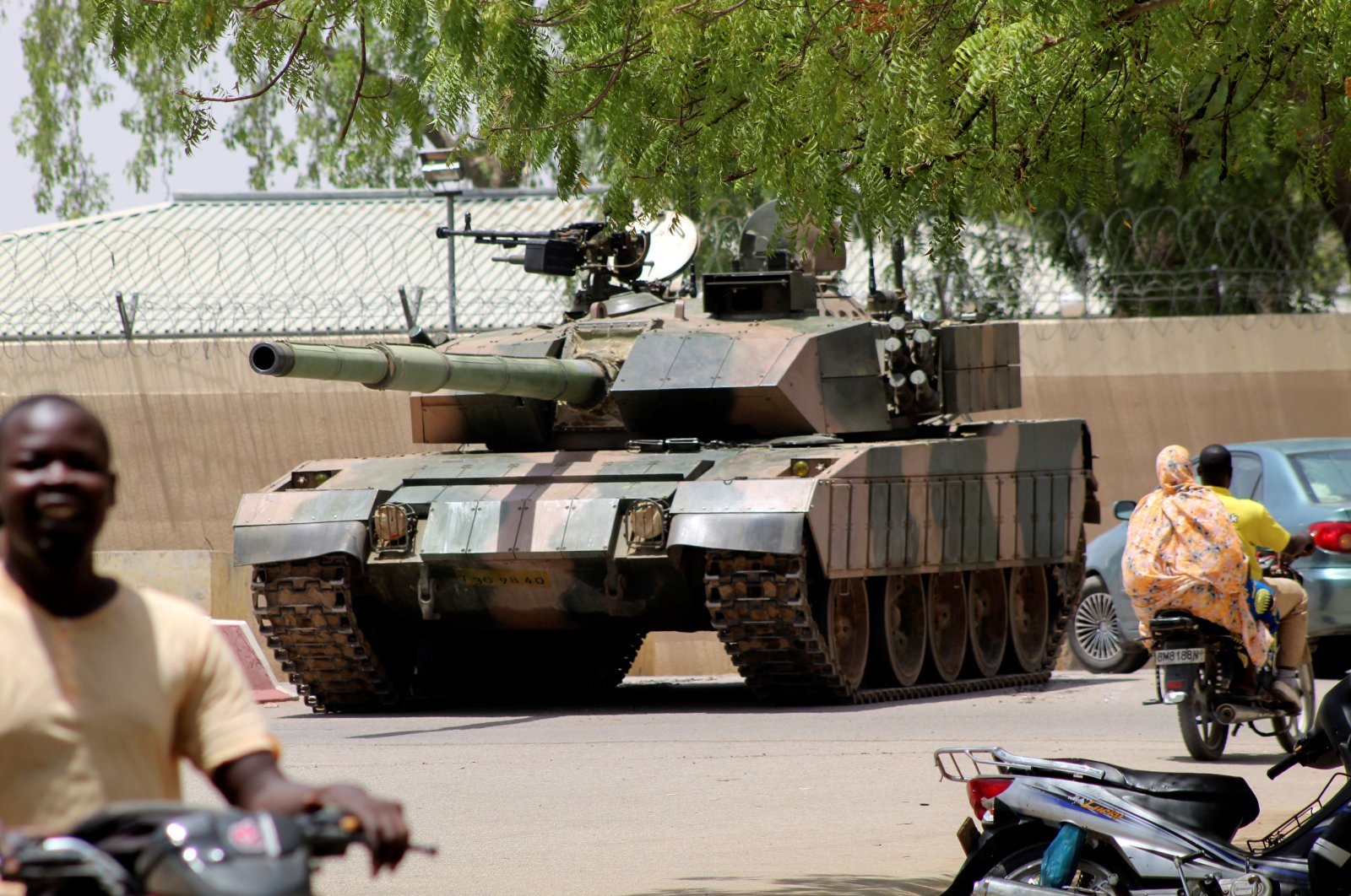 People drive past a Chad army tank near the presidential palace, as fighters from the rebel Front for Change and Concord in Chad (FACT) appeared to be moving toward the capital according to U.S. sources, N'djamena, Chad, April 19, 2021. (Reuters Photo)