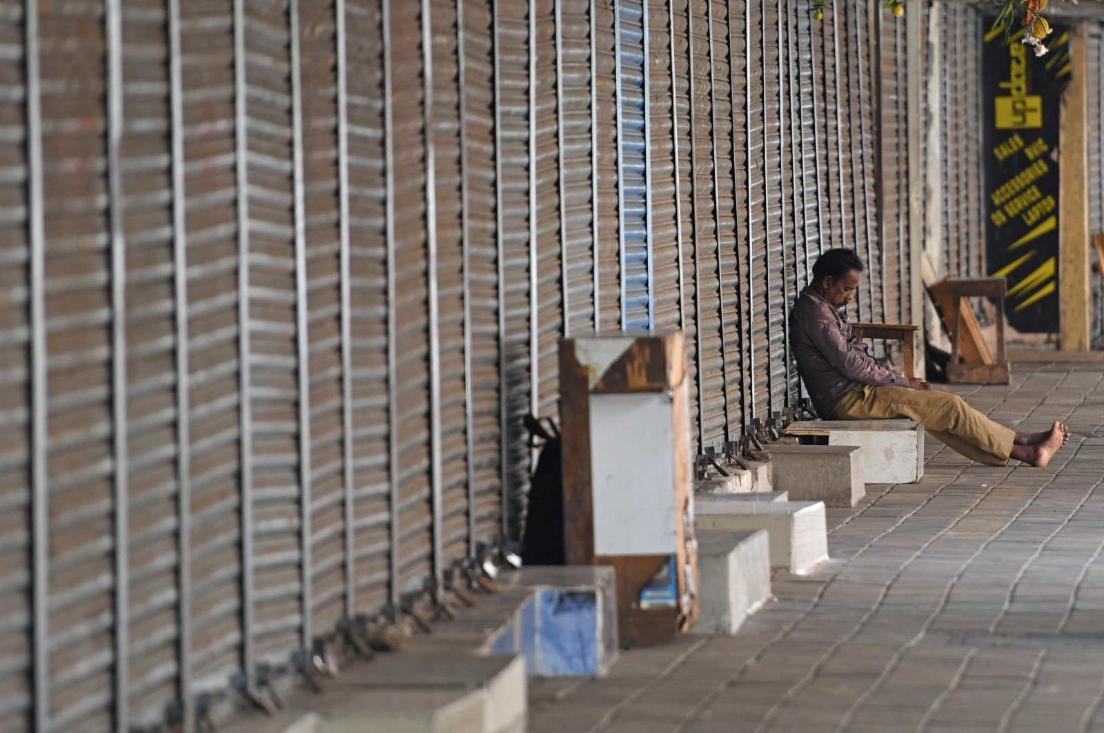 A man takes a nap amid closed shops during the Sunday lockdown imposed as a preventive measure against the spread of the COVID-19 coronavirus, Chennai, India, April 25, 2021. (AFP Photo)