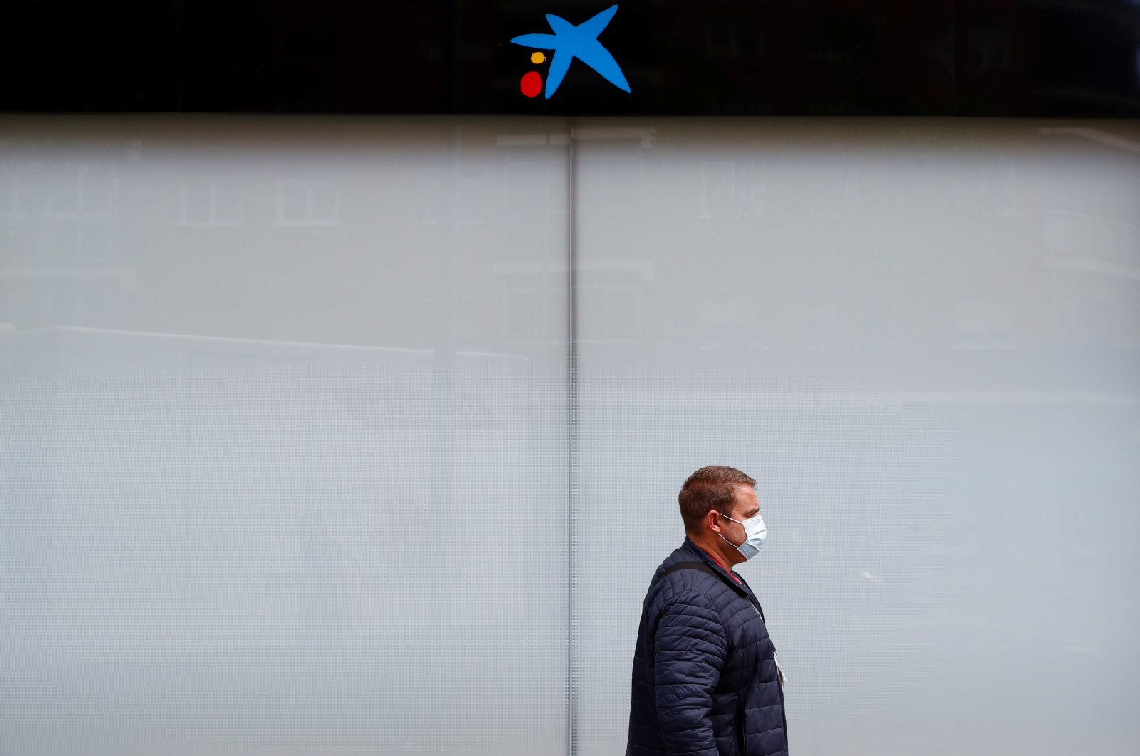 A person walks past a Caixabank's bank branch in Madrid, Spain, April 20, 2021. (Reuters Photo)