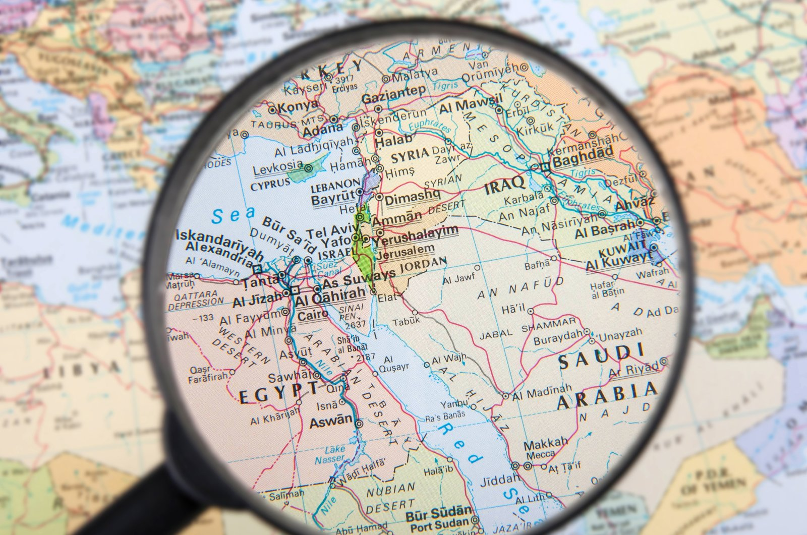 In this illustration photo, a magnifying glass provides a partial view of the Middle East. (Photo by Shutterstock)