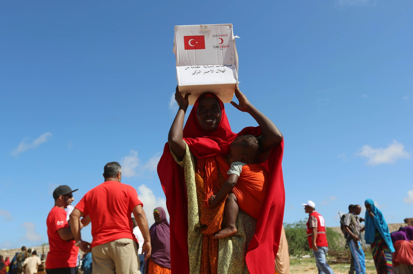 A displaced Somalian woman carries a box of food distributed by the Turkish Red Crescent in a camp in Mogadishu, Somalia, May 23, 2017. (REUTERS)