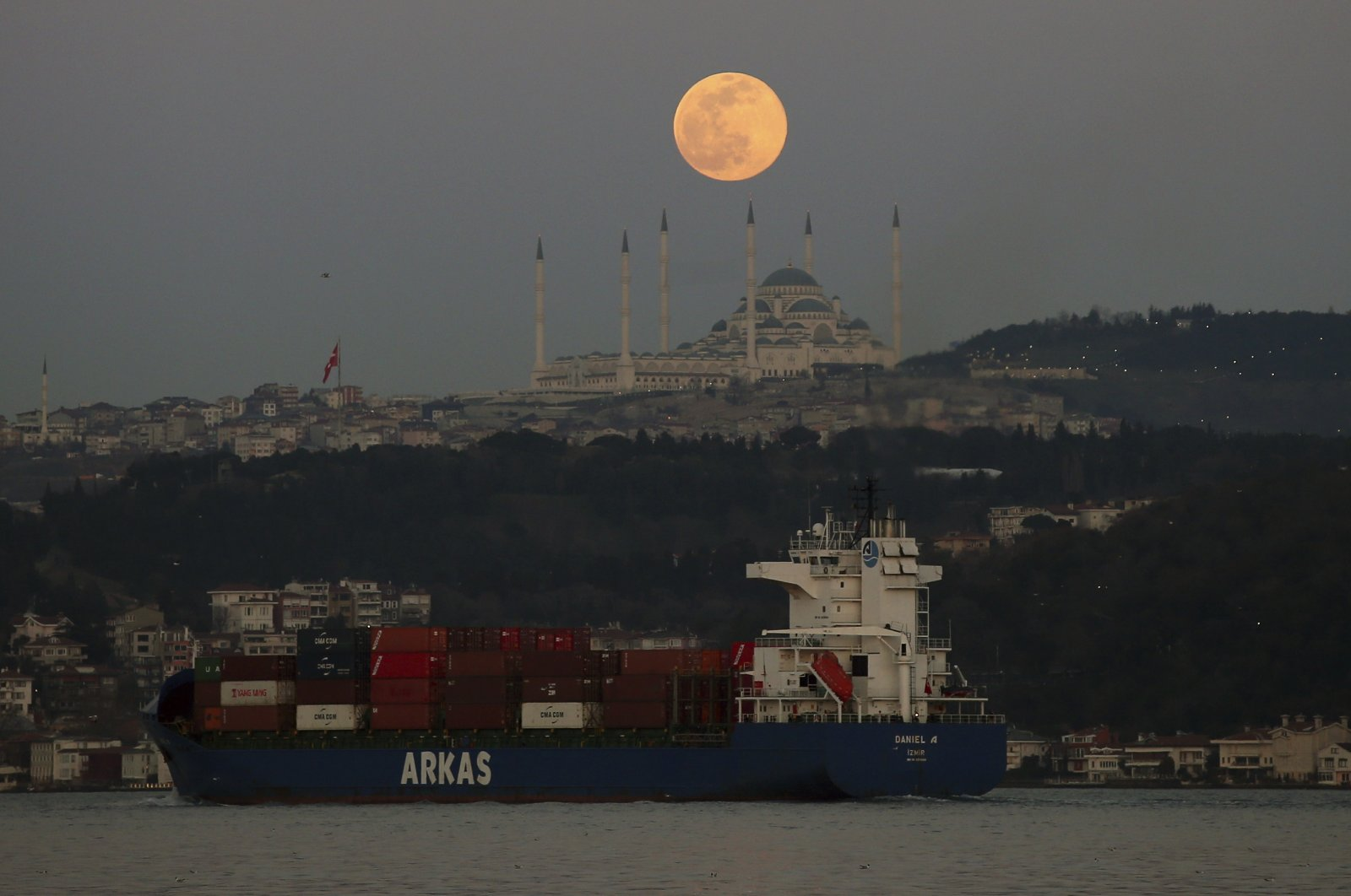 A container ship crosses the Bosporus Strait as the full moon rises over the sky in Istanbul, Turkey, March 28, 2021. (AP Photo)