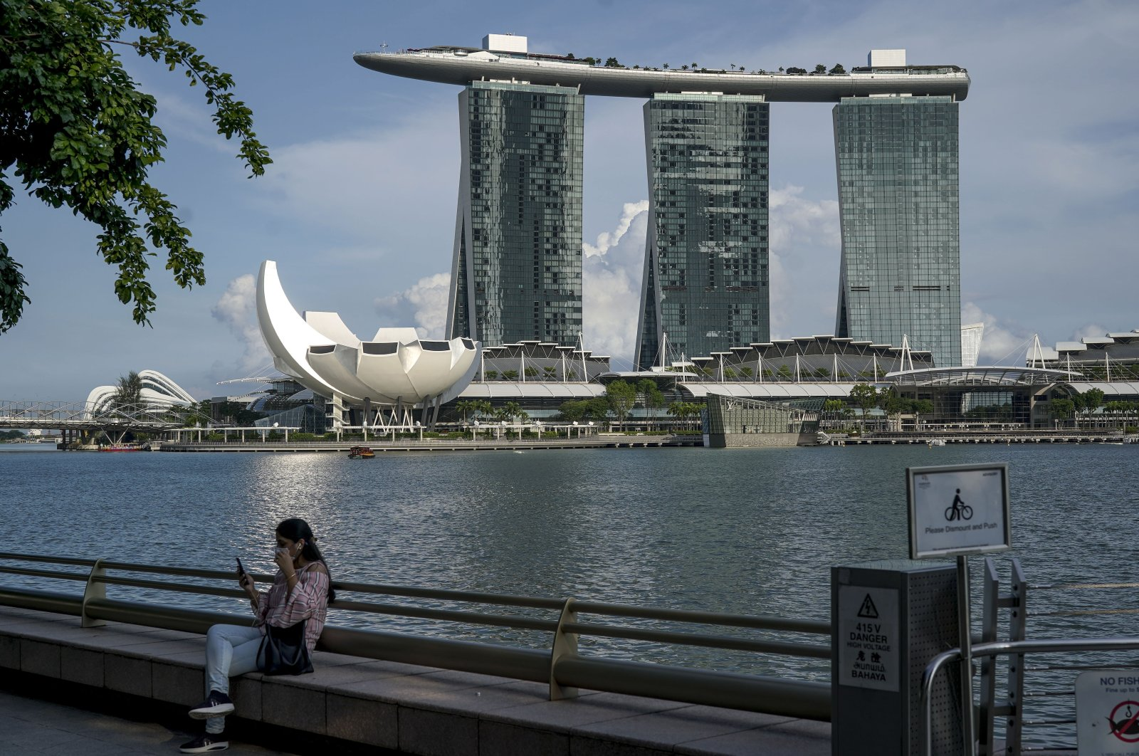 A woman sits along a ledge pictured in front of Marina Bay Sands Hotel in Singapore, April 14, 2021. (EPA Photo)