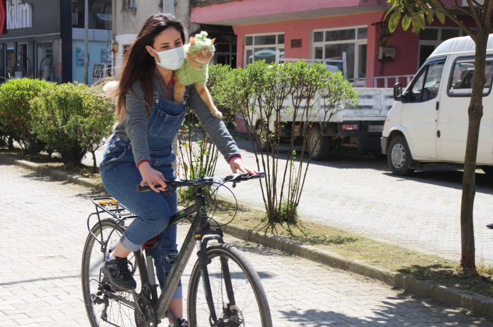 Özge Kübra Teymur bikes along a road with her cat Azman resting on her shoulders, Rize, Turkey, April 20, 2021. (DHA Photo)