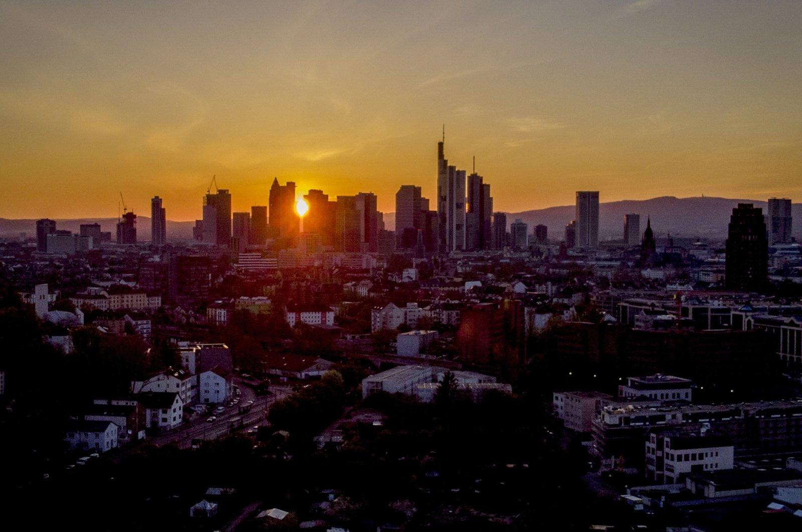The setting sun shines through buildings in the banking district of Frankfurt, Germany, April 25, 2021. (AP Photo)