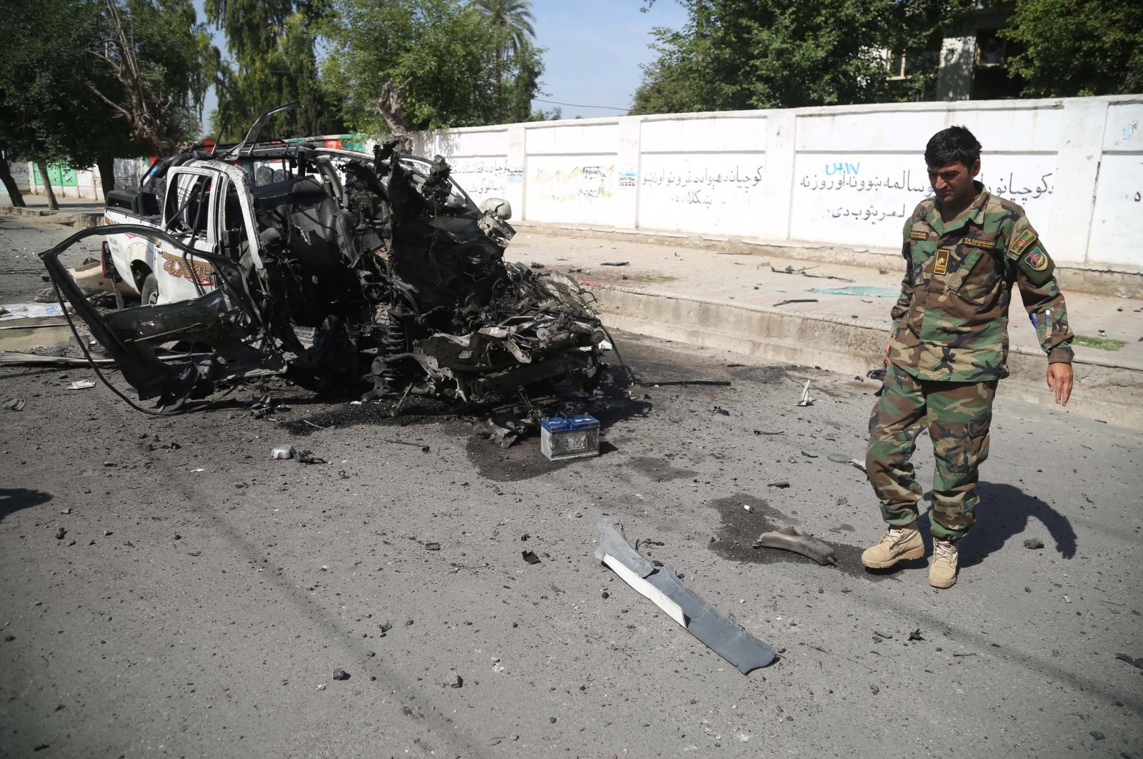 Afghan security officials inspect the scene of a bomb blast that targeted a vehicle of the Afghan National Army, in Jalalabad, Afghanistan, April, 26, 2021. (EPA Photo)