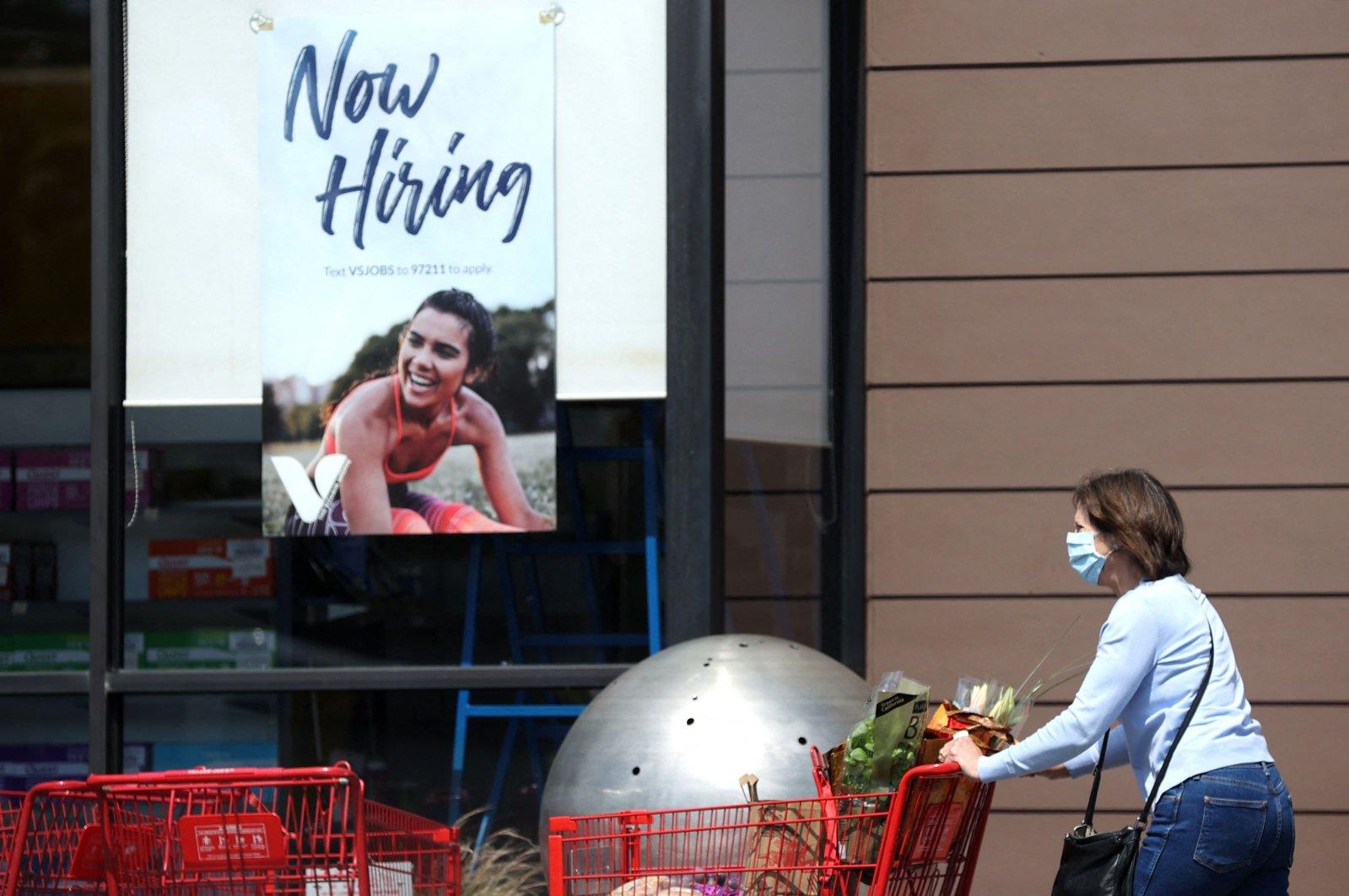 A pedestrian walks by a now hiring sign in Larkspur, California, U.S., April 2, 2021. (AFP Photo)