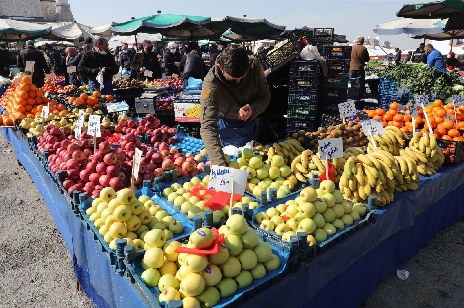 A vendor wearing a protective mask arranges his stall at a local market, amid the COVID-19 outbreak in Ankara, Turkey, Feb. 22, 2021. (AFP Photo)