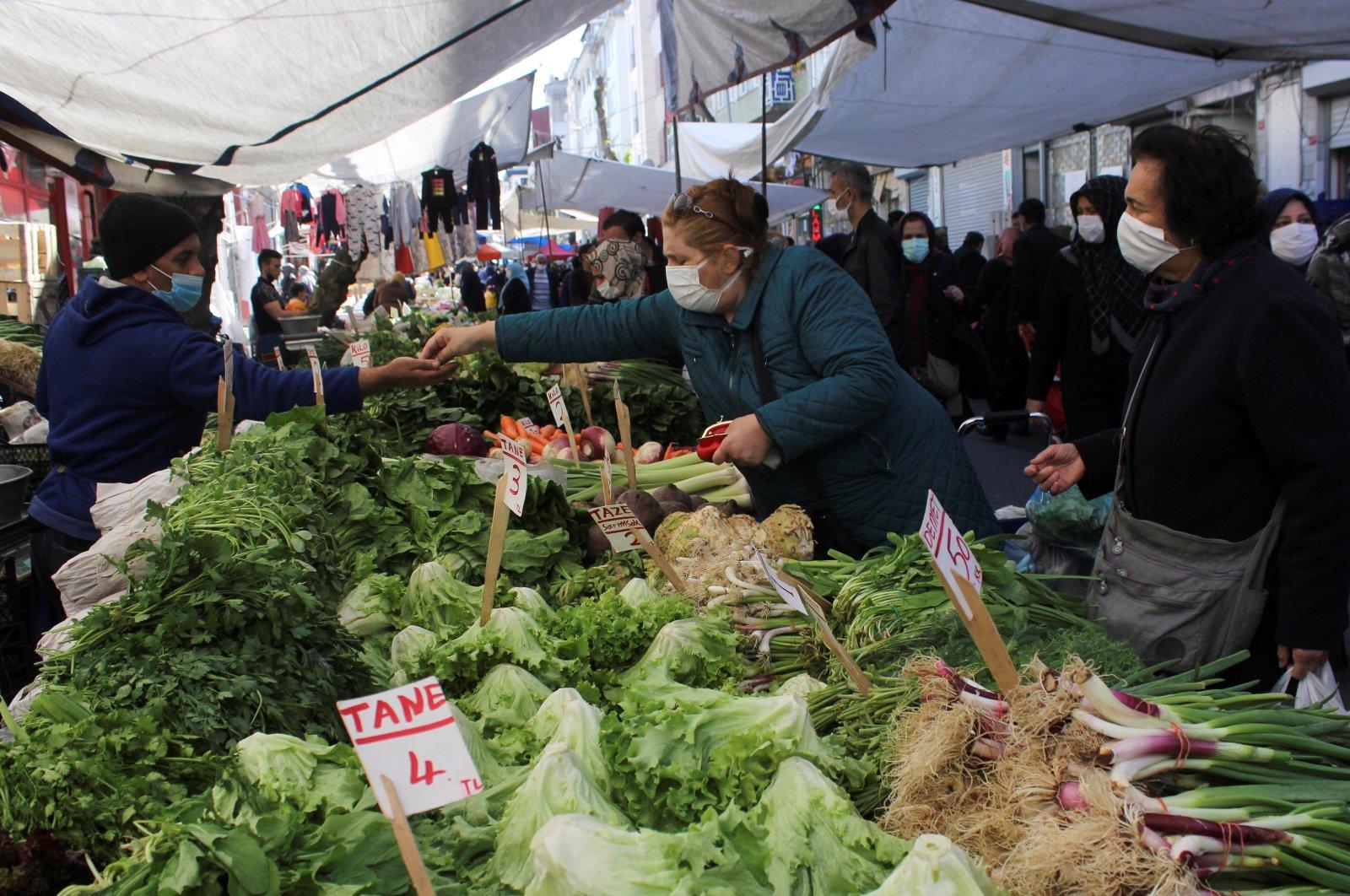 People wearing protective face masks shop at a fresh food market amid the coronavirus disease (COVID-19) pandemic, Istanbul, Turkey April 26, 2021. (Reuters Photo)