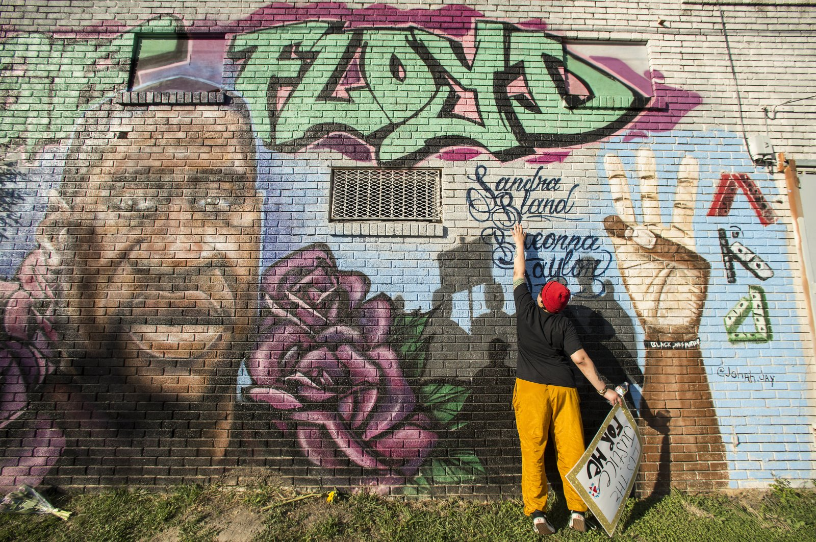 Daryel Simmons reaches up to touch the names of Sandra Bland and Breonna Taylor at a George Floyd memorial mural, Houston, U.S., April 20, 2021. (AP Photo)