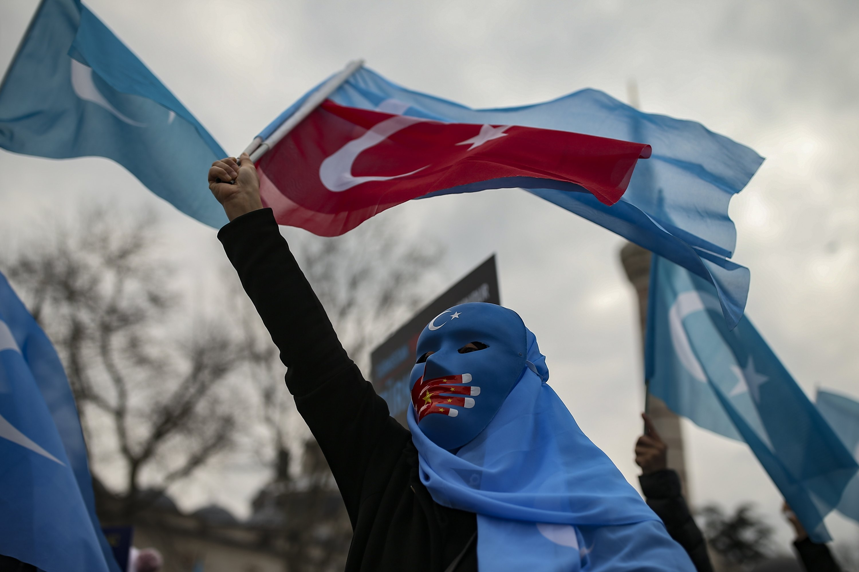 A protester from the Uyghur community living in Turkey waves a Turkish flag during a protest against China's treatment of Uyghurs, in Istanbul, Turkey, March 25, 2021. (AP Photo)