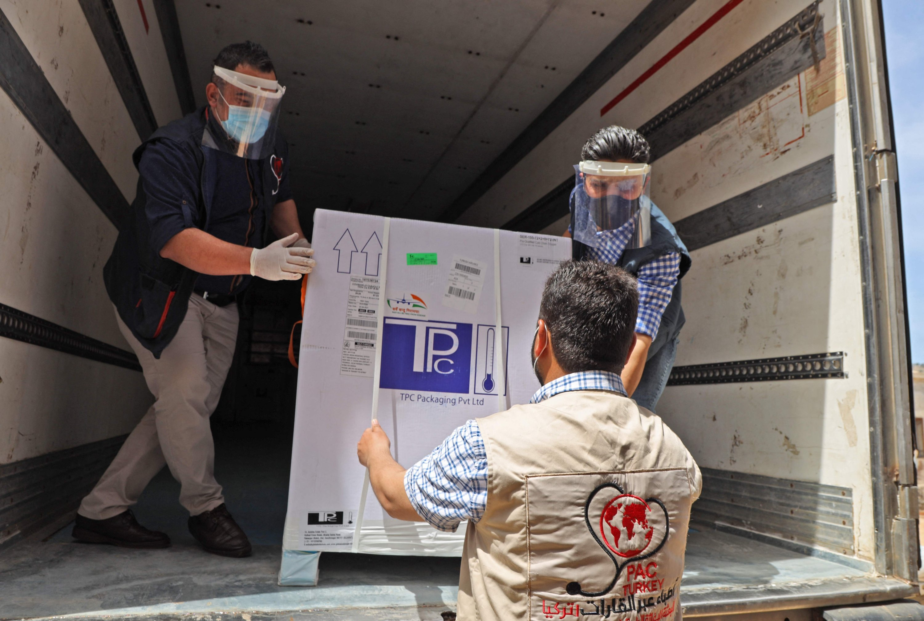 Staff of the Physicians Across Continents group unload the first batch of AstraZeneca COVID-19 vaccines at Bab al-Hawa border crossing between Syria and Turkey in Syria's opposition-held northwestern Idlib, April 21, 2021. (AFP Photo)