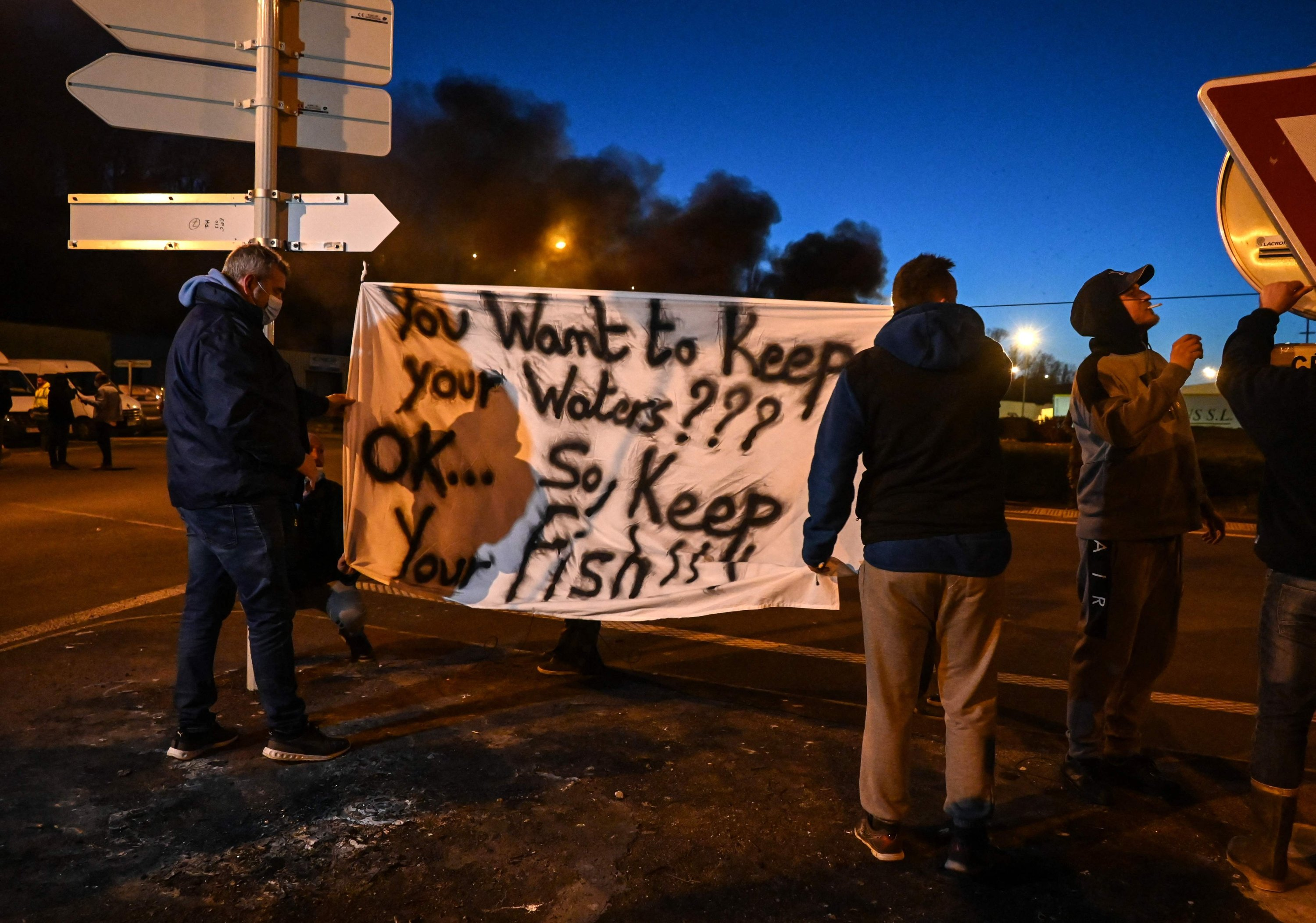 French fishermen stand near a banner as they gather as part of a protest action against the delay in granting licenses to access British waters at the port of Boulogne-sur-Mer on April 22, 2021. (AFP Photo)