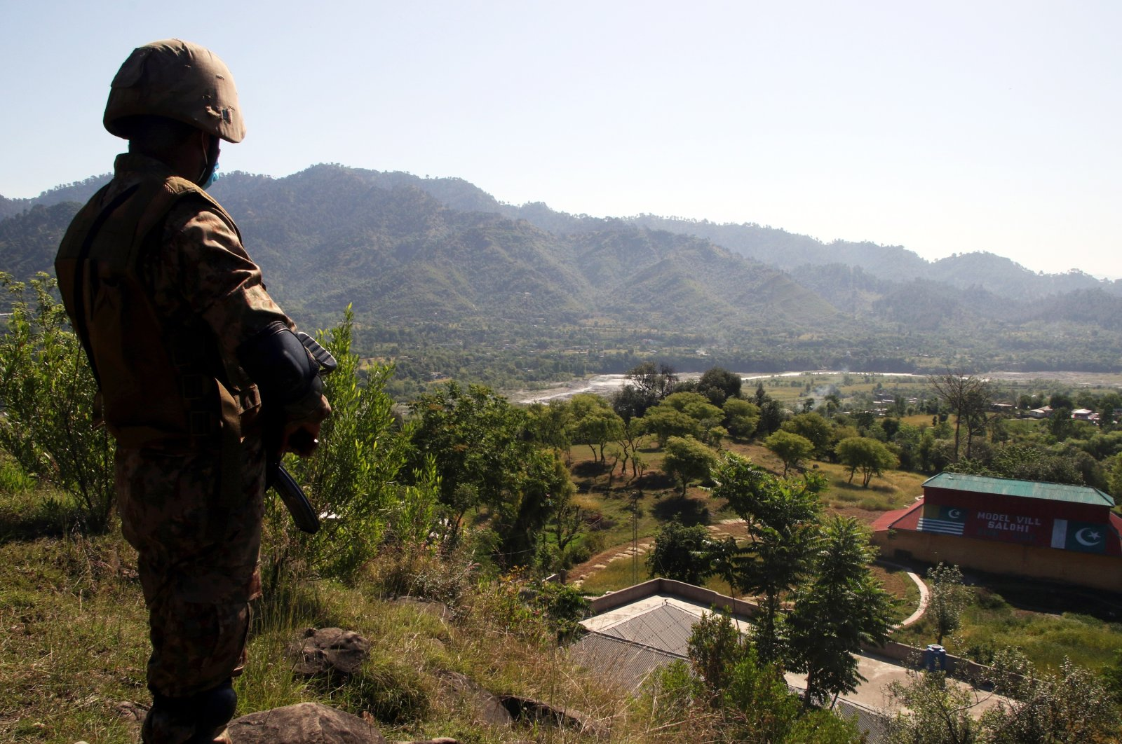 A Pakistani Army soldier stands near a house that was damaged in cross border shelling before the cease-fire, in Salohi village, Poonch district near the Line of Control, Pakistani administered Kashmir, April 26, 2021. (EPA Photo)