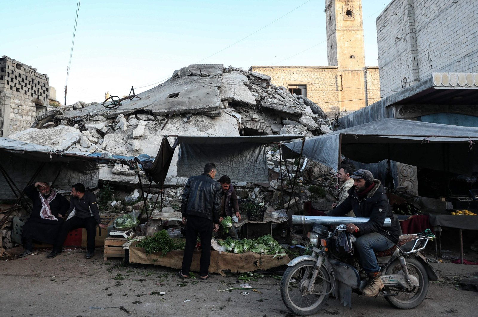 Syrians buy food products at a market ahead of iftar, the evening meal that ends the daily fast at sunset, on the second day of Ramadan, in the war-ravaged city of Ariha, located near the strategic M4 highway, in the southern countryside of the Idlib province, Syria, April 15, 2021. (AFP Photo)