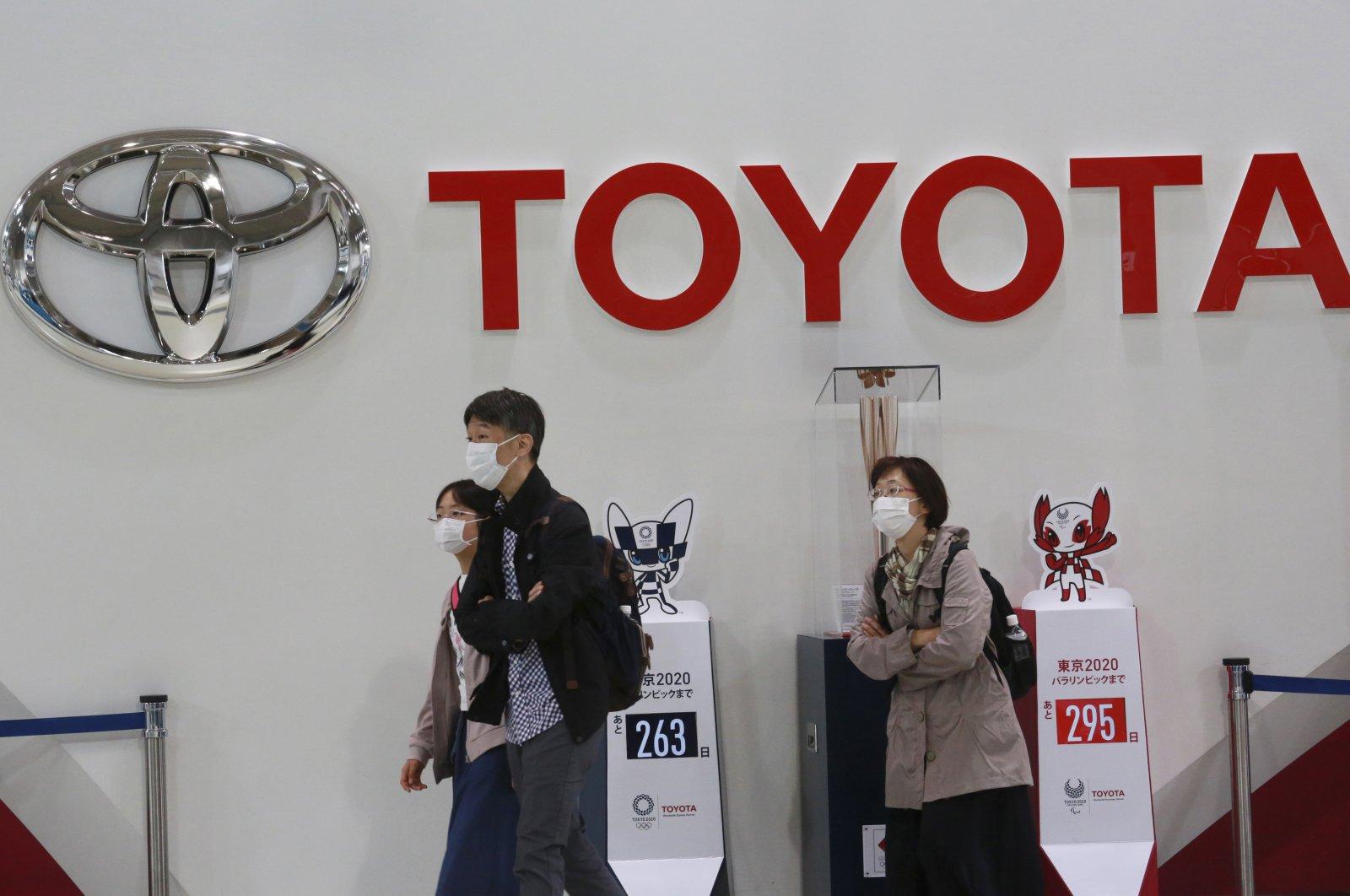 Visitors walk around a Toyota showroom in Tokyo, Japan, Nov. 2, 2020. (AP Photo)