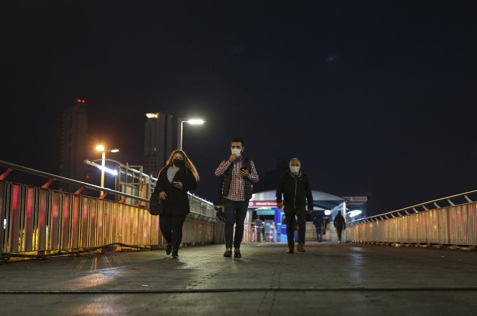 People wearing protective masks walk on an overpass, in Istanbul, Turkey, April 26, 2021. (AP PHOTO)