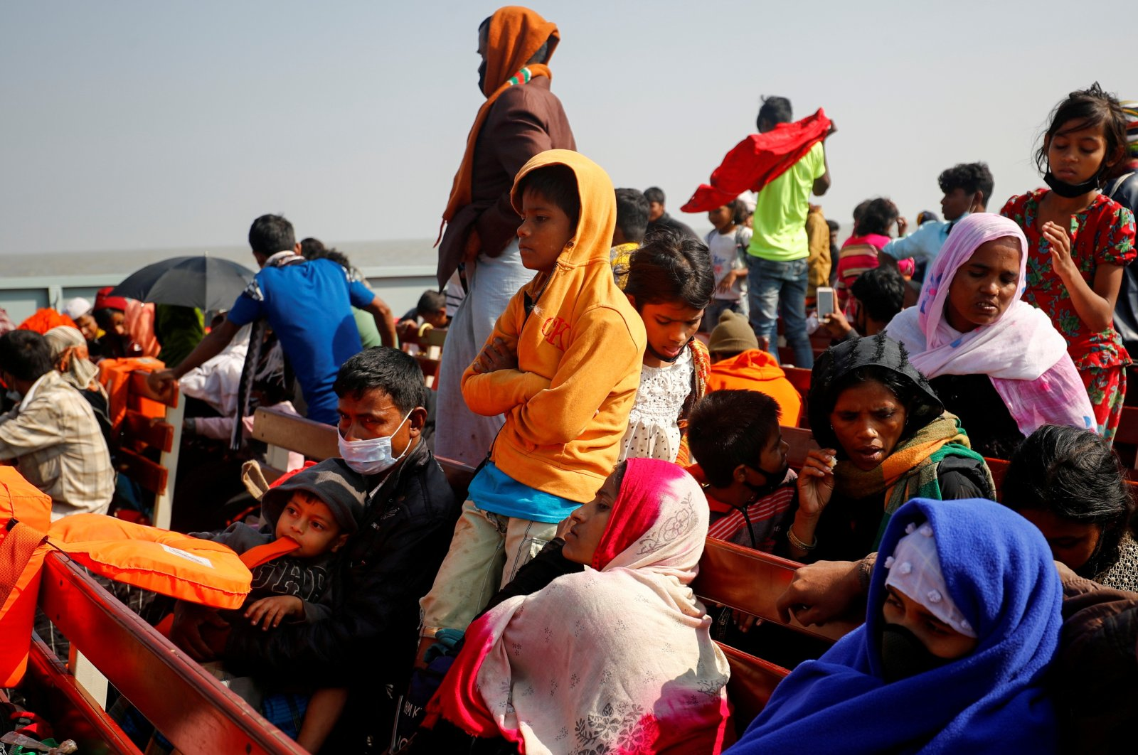 Rohingya refugees sit on wooden benches of a navy vessel on their way to the Bhasan Char island in Noakhali district, Bangladesh, Dec. 29, 2020. (Reuters/Mohammad Ponir Hossain/File Photo/File Photo)