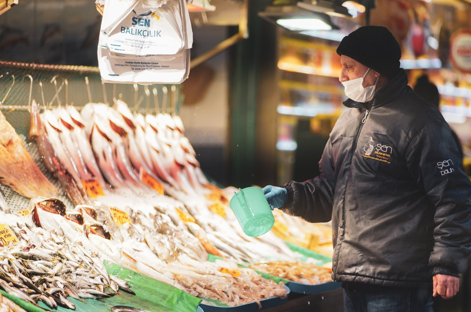 A fisherman wearing a protection mask against the COVID-19 pandemic stands at the counter in a fish market in Istanbul, Turkey, Feb. 4, 2020. (Shutterstock Photo)