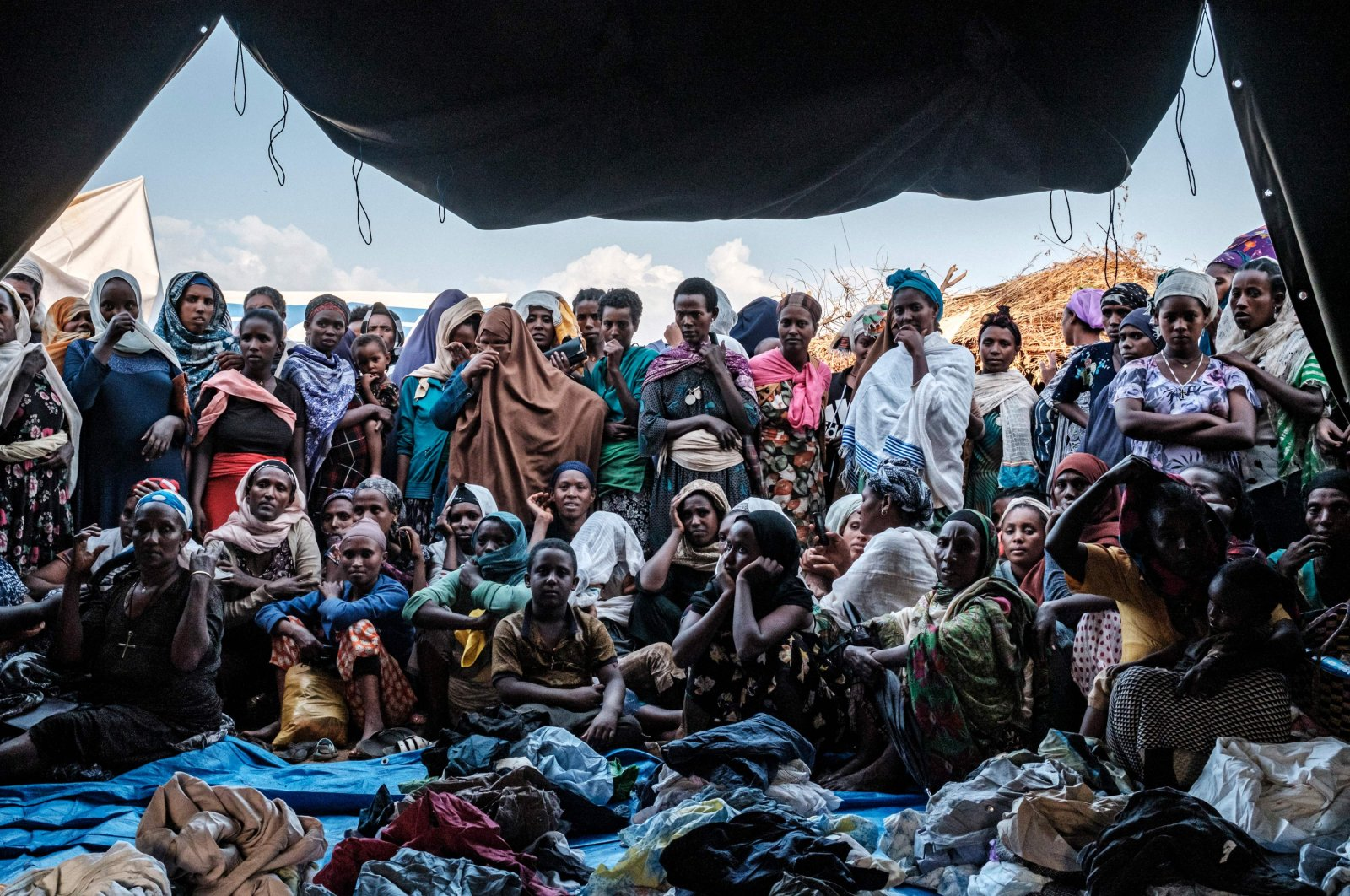 Internally Displaced People (IDP), fleeing from violence in the Metekel zone in Western Ethiopia, gather outside a tent where clothes are being distributed at a camp in Chagni, Ethiopia. Jan. 26, 2021. (AFP Photo)