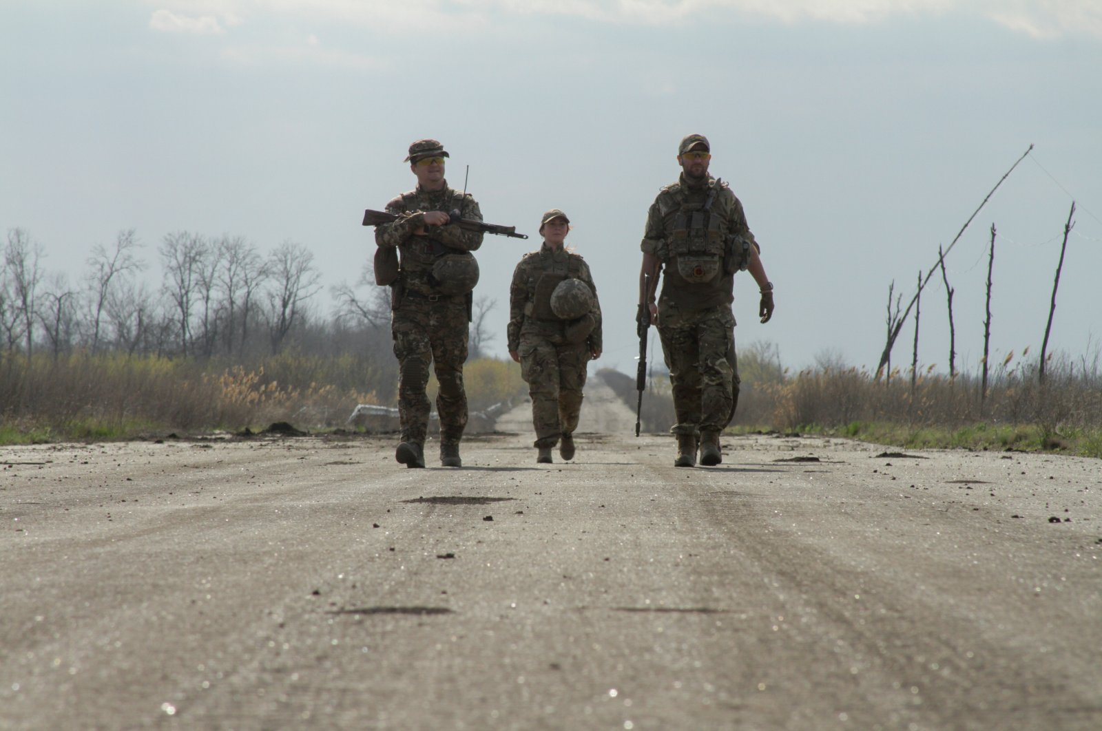 Service members of the Ukrainian armed forces walk along a road near the line of separation outside the rebel-controlled city of Donetsk, Ukraine, April 26, 2021. (Reuters/Serhiy Takhmazov Photo)
